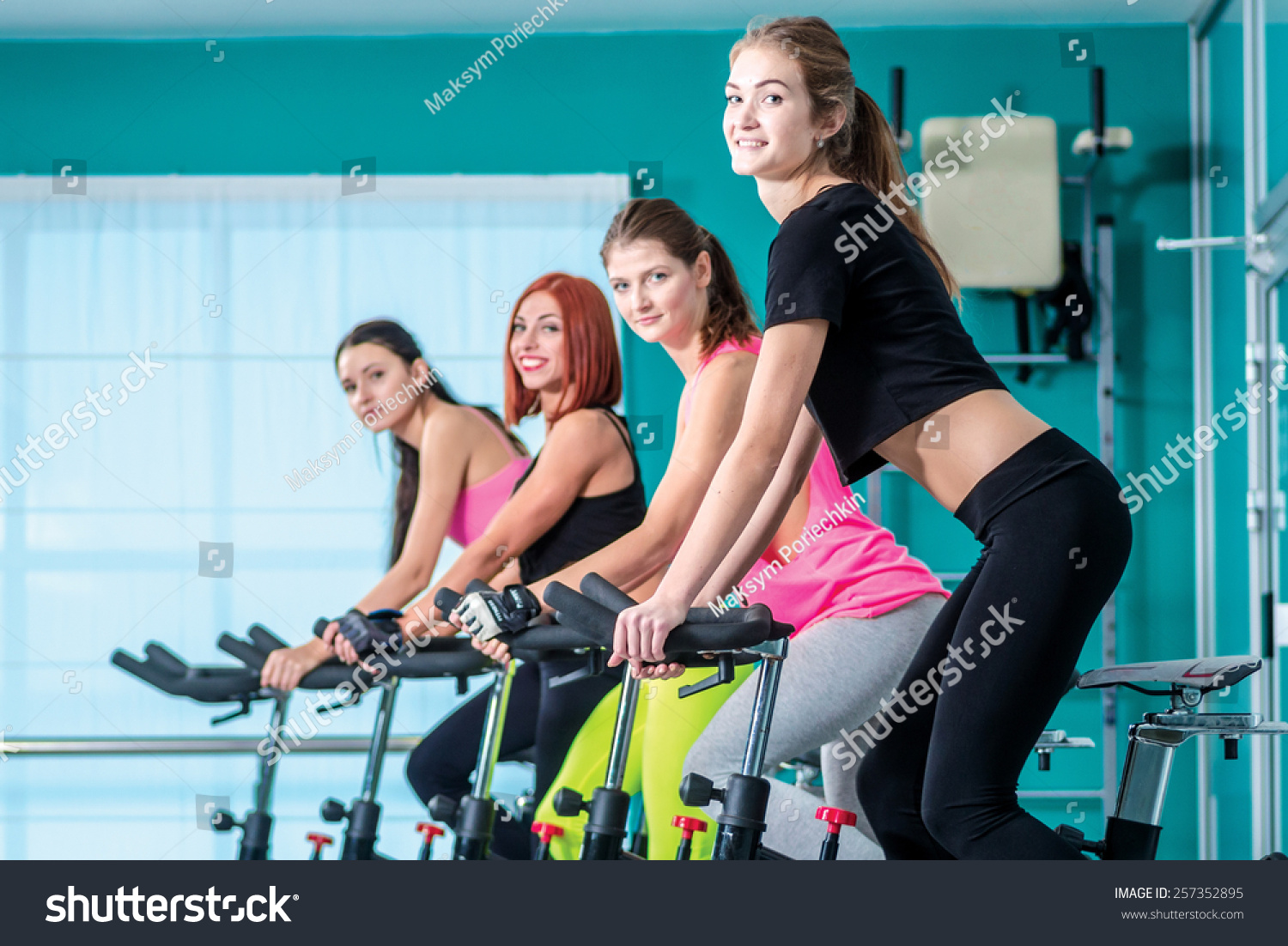 Fitness workout in the gym Athletic girl pedaling on the simulator until her four girlfriends athletes pedaling on a stationary bike at the gym