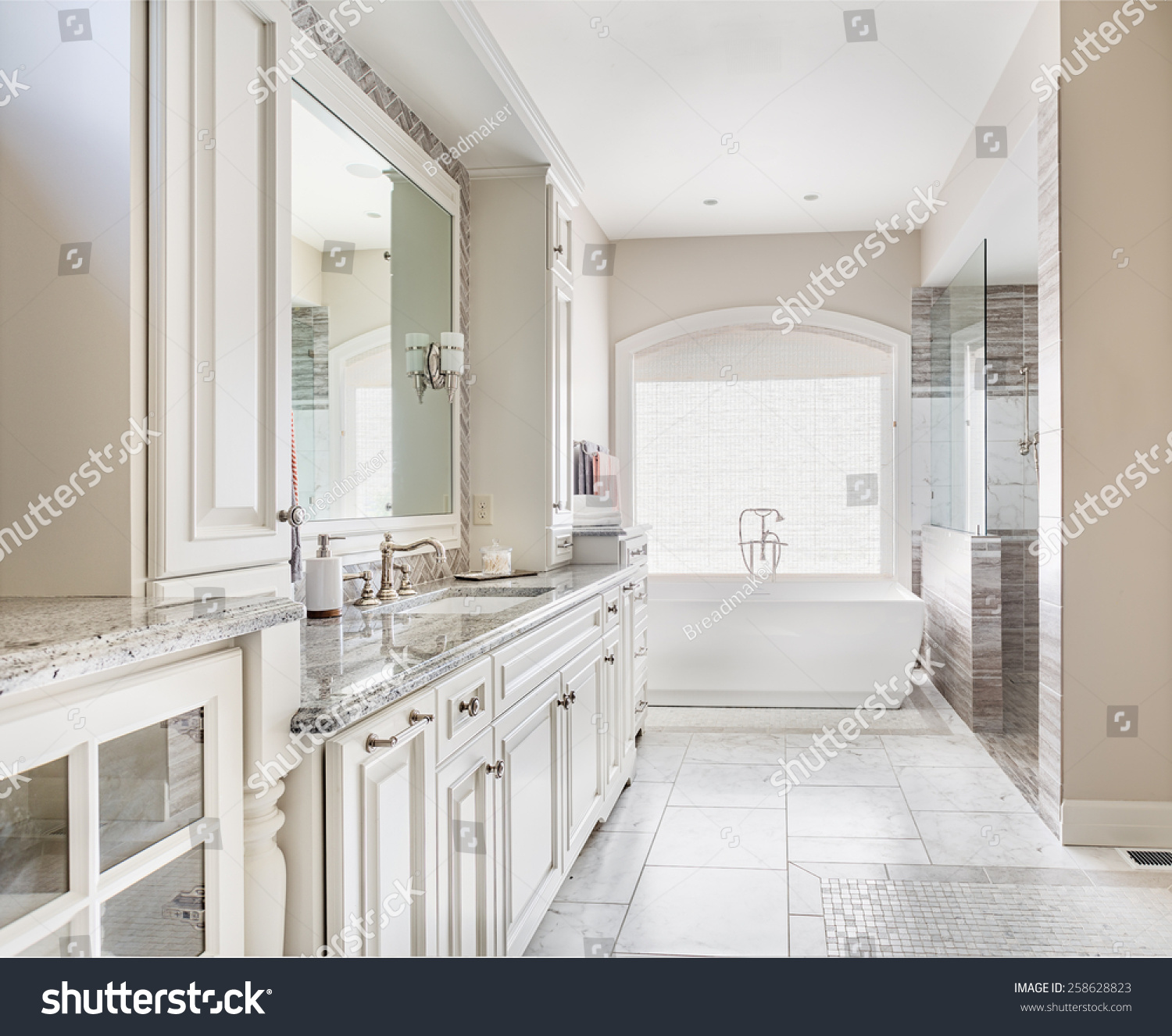 Large Bathroom In Luxury Home With Two Sinks, Tile Floors, Fancy Cabinets, Large Mirrors, And