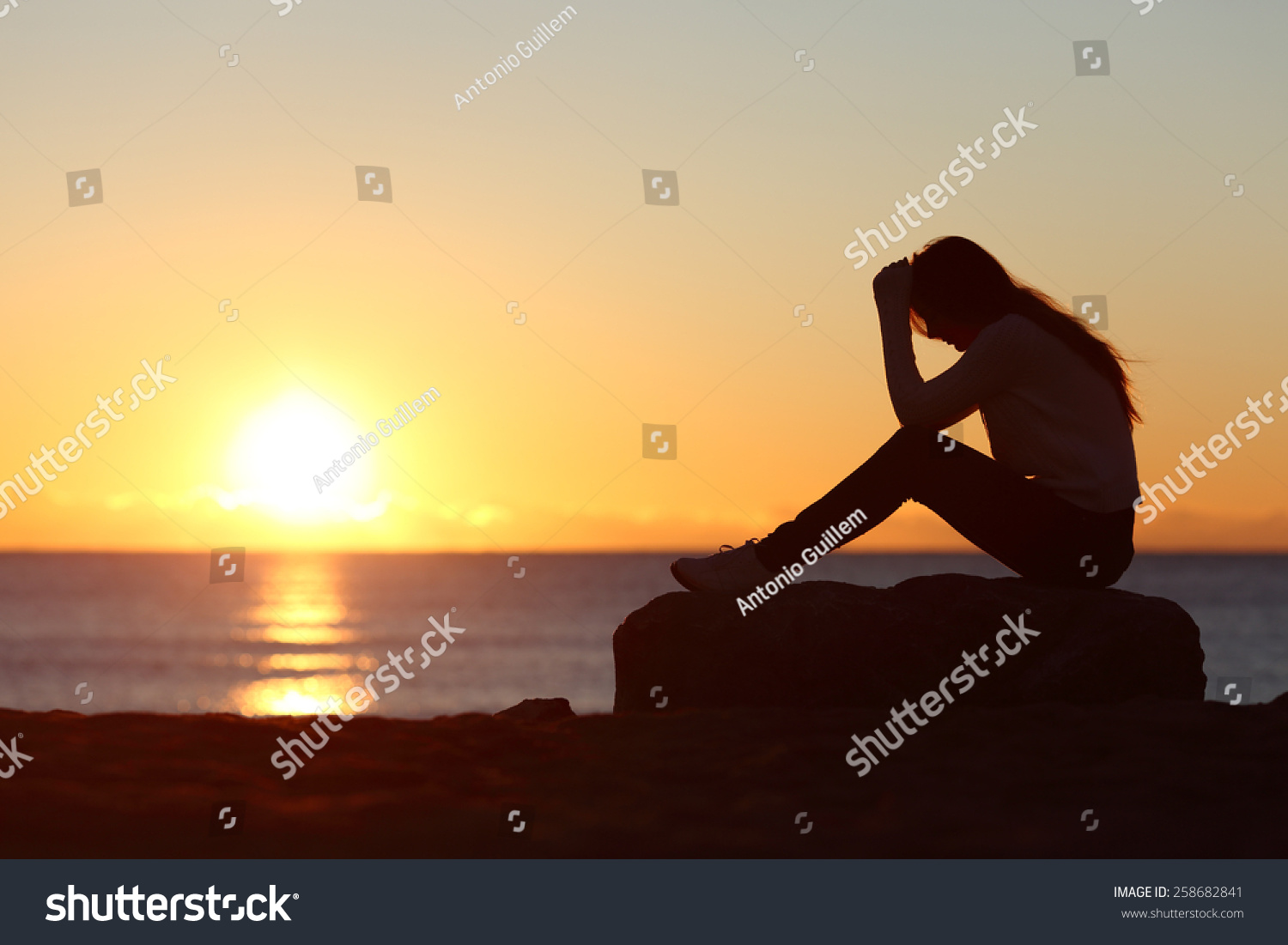 Sad woman silhouette worried on the beach at sunset with the sun in the background #258682841