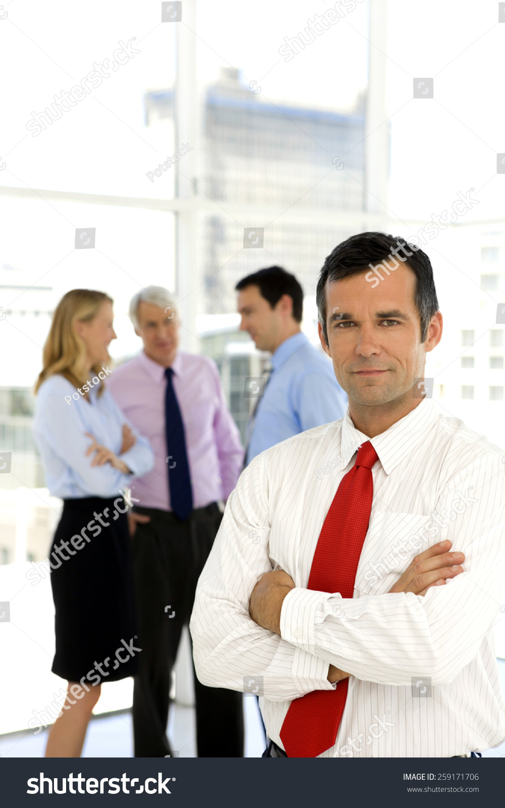 06f4a59339e0 Businessman with arms crossed standing on foreground while other business  people talk in the background