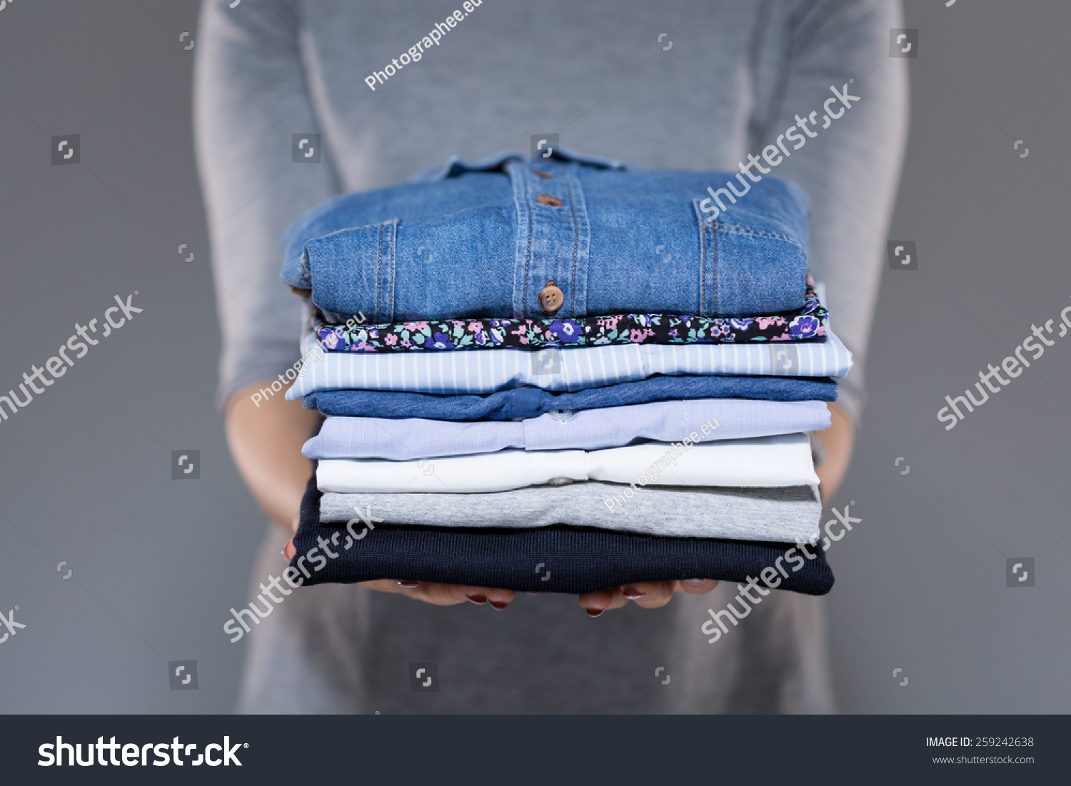 Woman holding folded clothes in hands #259242638