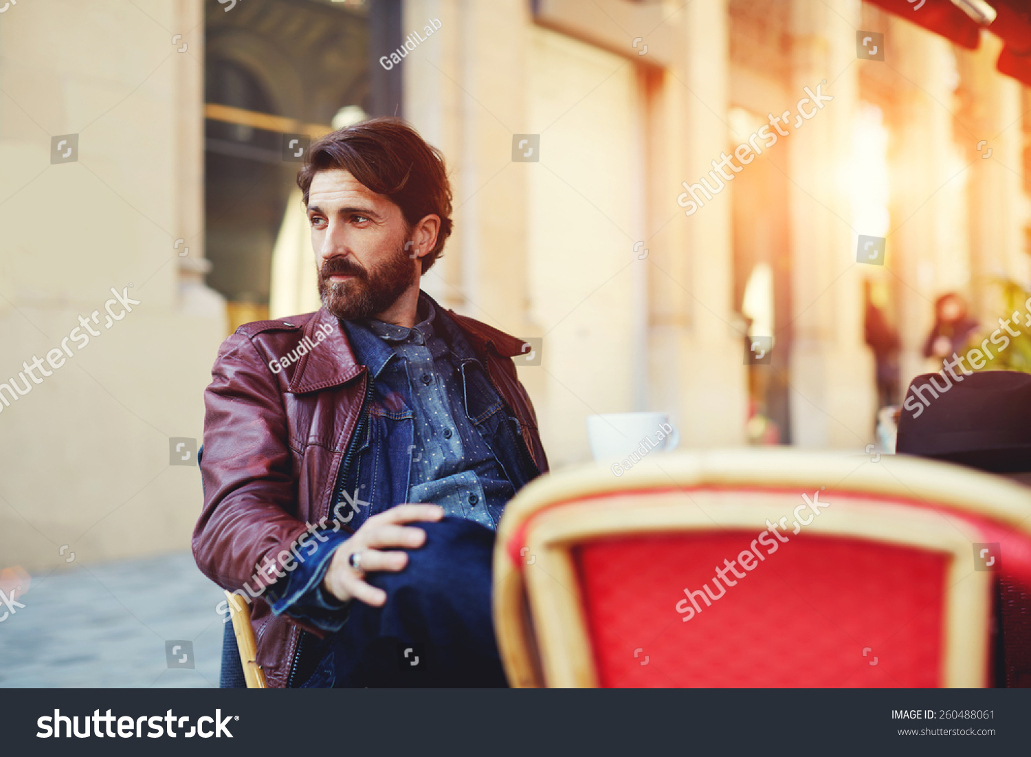 Portrait of handsome and stylish man with beard enjoying a cup of coffee in a coffee shop adult fashionable hipster having coffee in beautiful cafe terrace at sunny day flare sun light