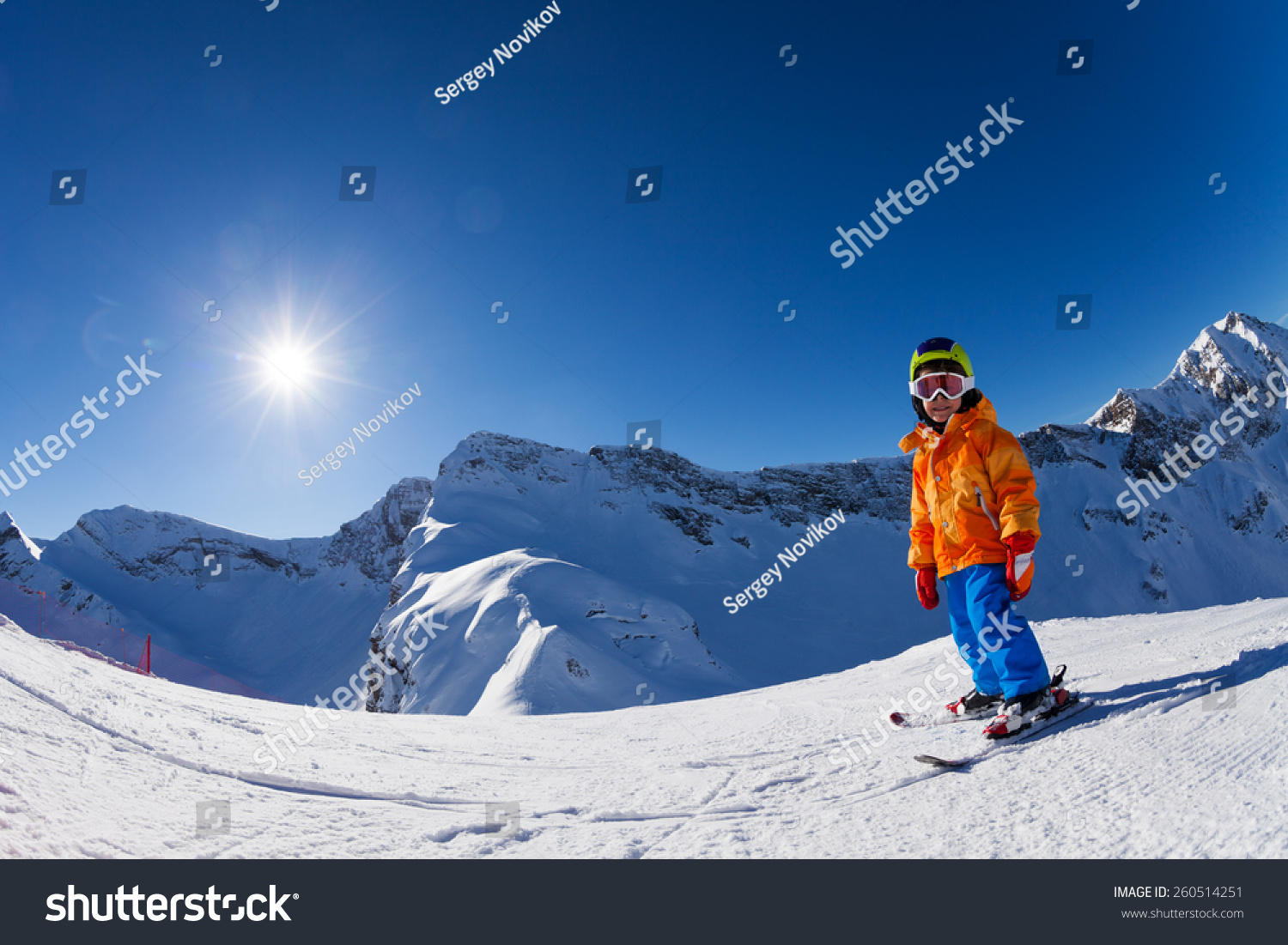 Fisheye view of boy skiing on mountain slope #260514251