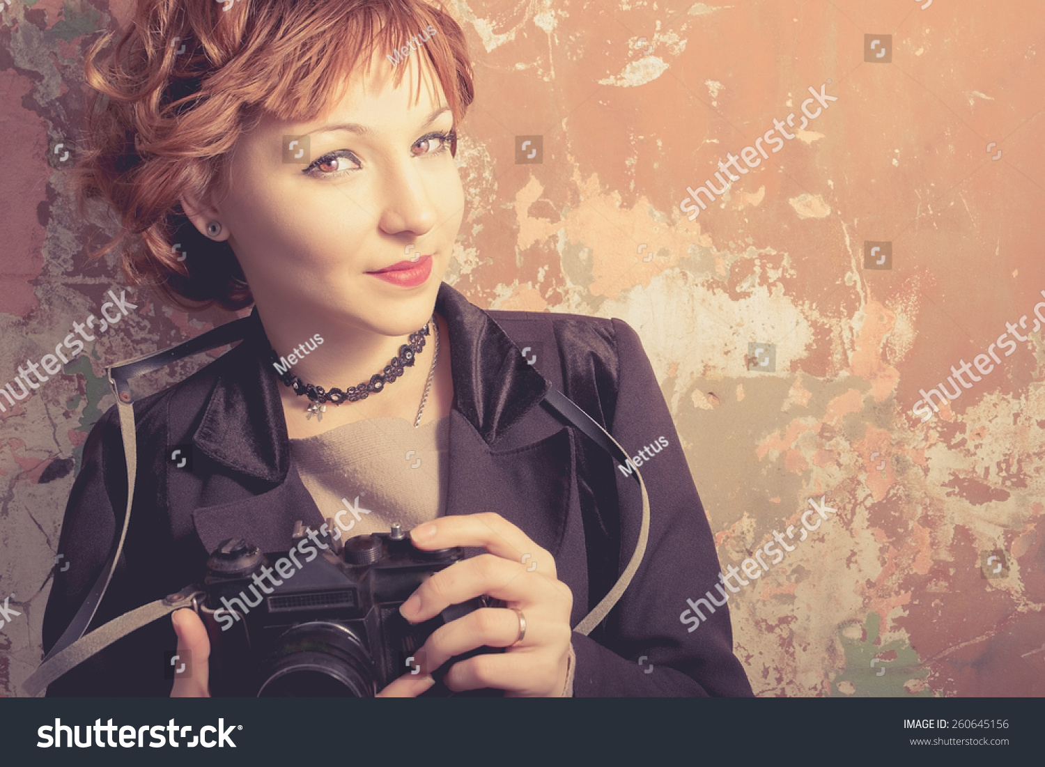 Redhead hipster woman taking photos with retro film camera outdoors.