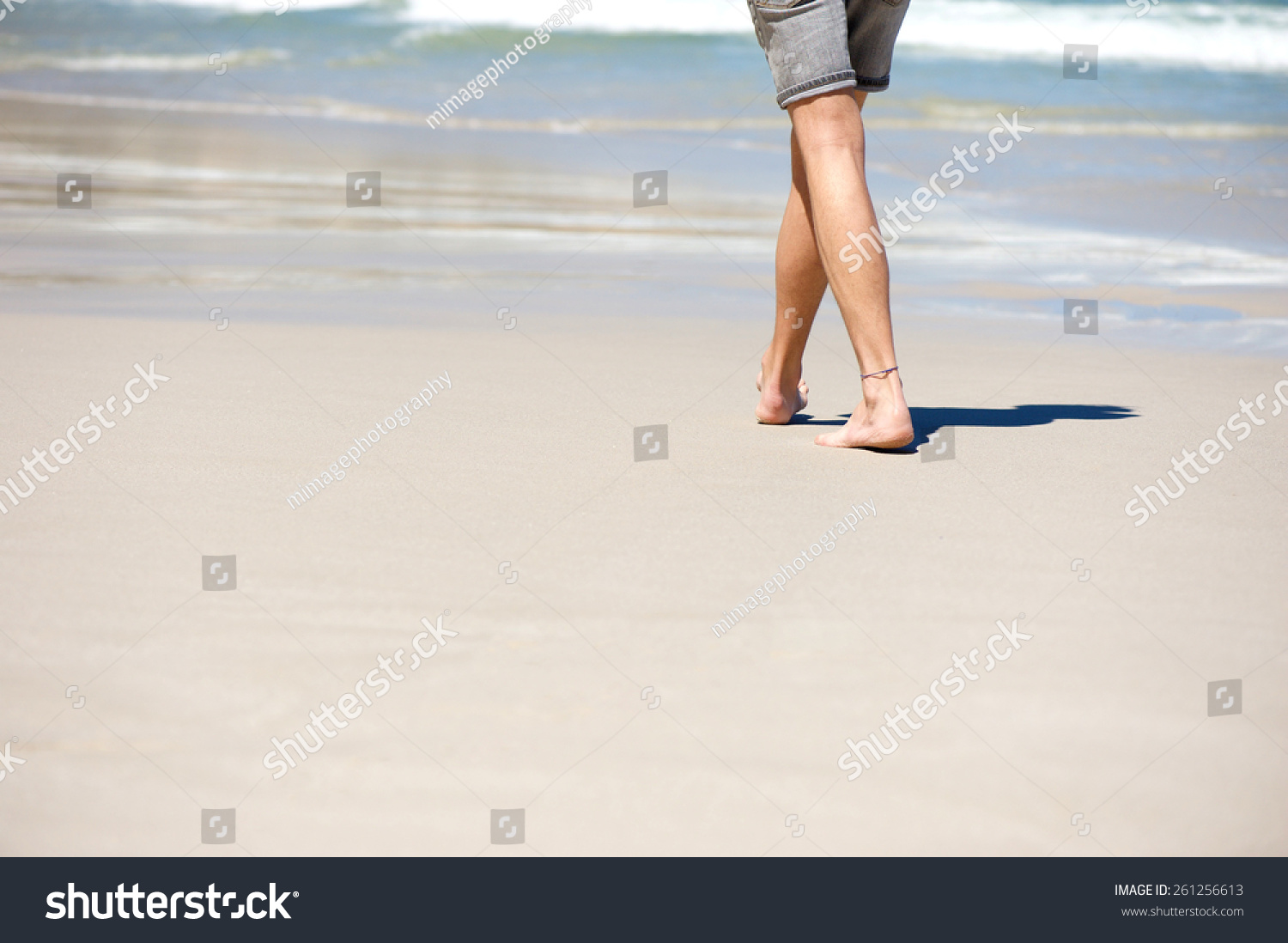 Close up man walking barefoot on vacation at the beach  #261256613