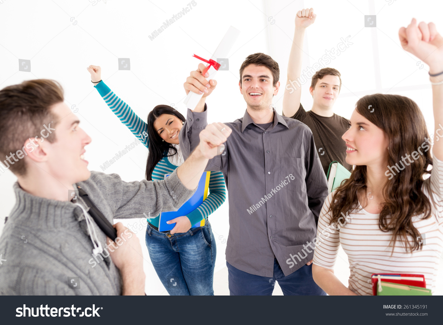 beautiful smiling young man student diploma stock photo  a beautiful smiling young man student diploma a happy group of his friends is