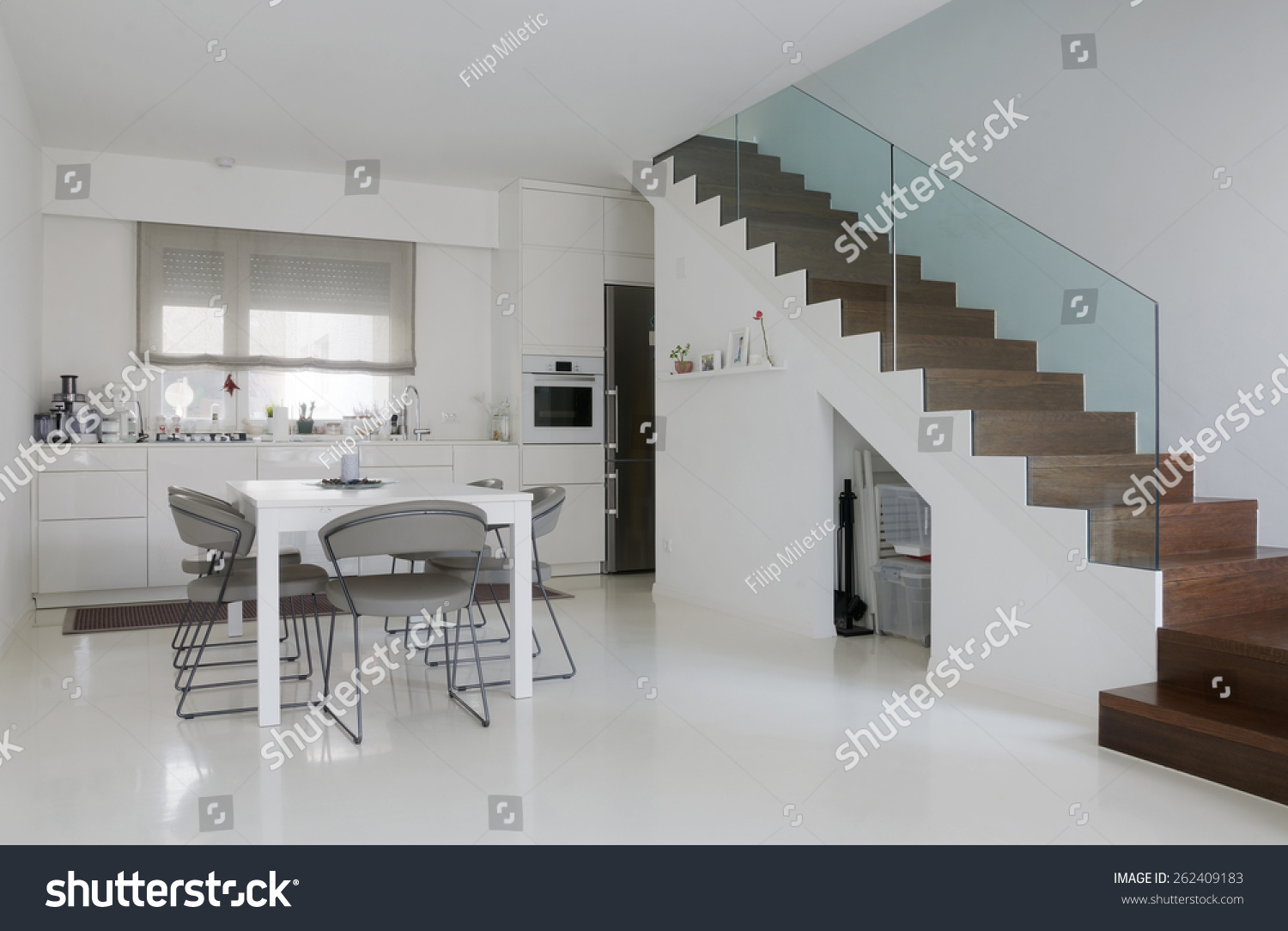 stock photo white kitchen and dining room with white epoxy floor and wooden stairs 262409183