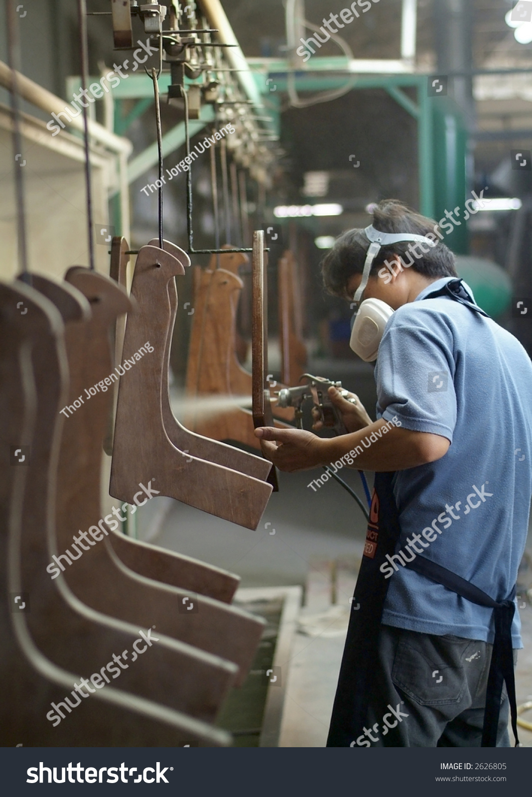 Factory Worker Spray Painting Furniture Parts At An