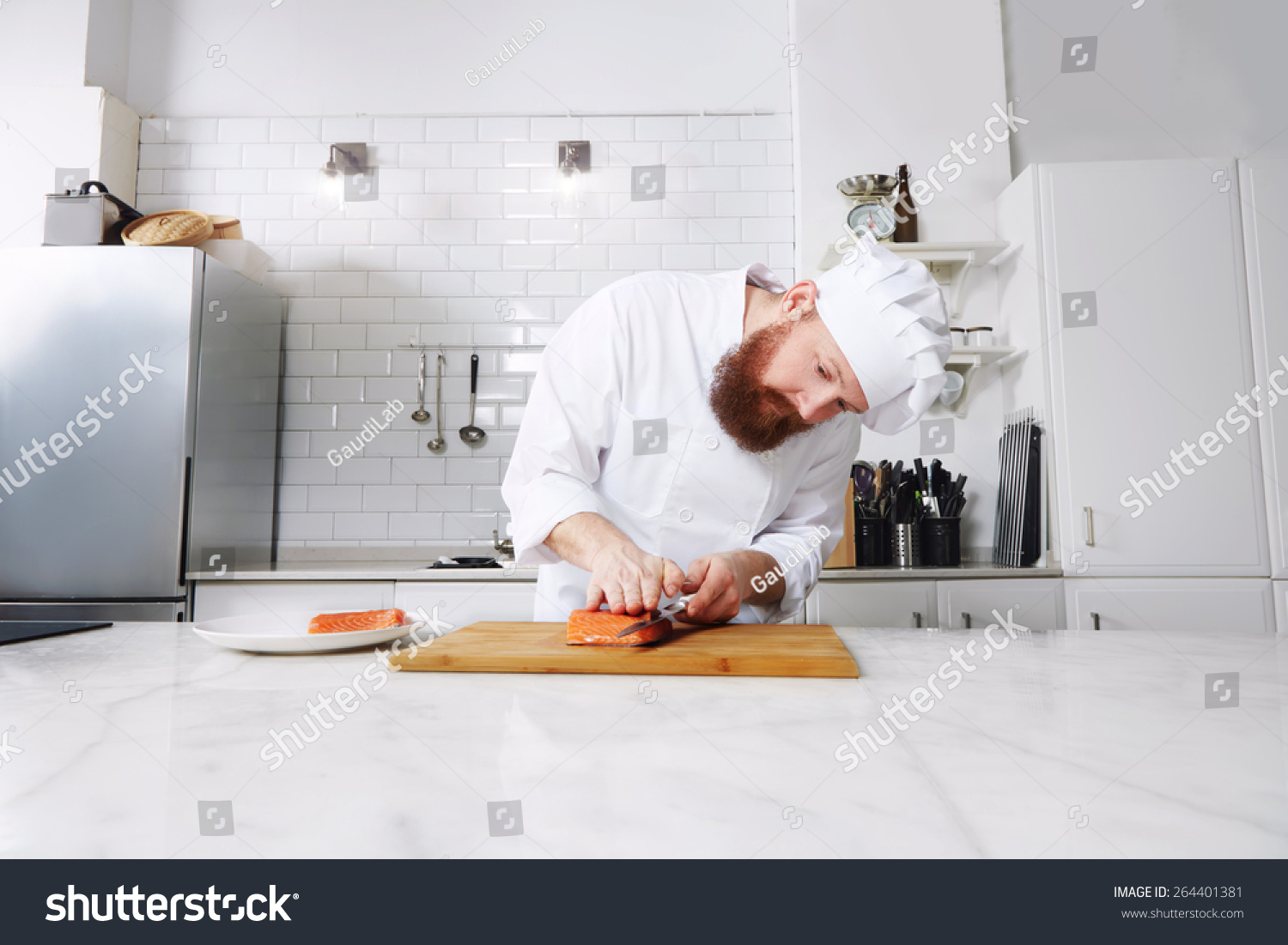 Portrait Of Professional And Experienced Chef Cook In Uniform Diligently Cutting Salmon Fish On