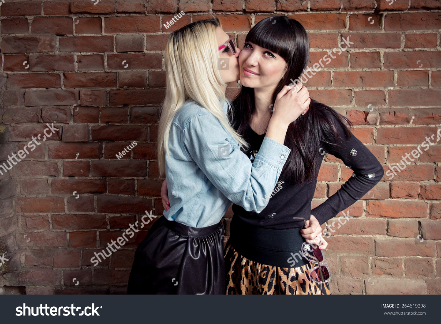 Two girls kissing outdoors near red brick wall
