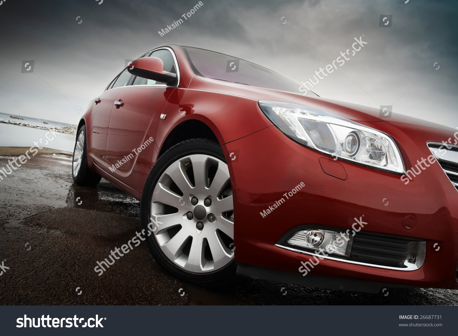 Cherry red car front detail with big light alloy wheel stock photo