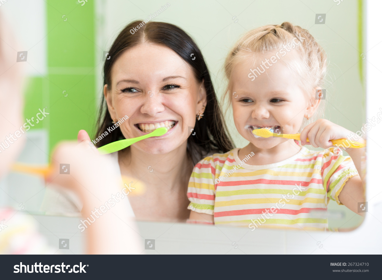Hygiene Happy mother and child girl brushing teeth together