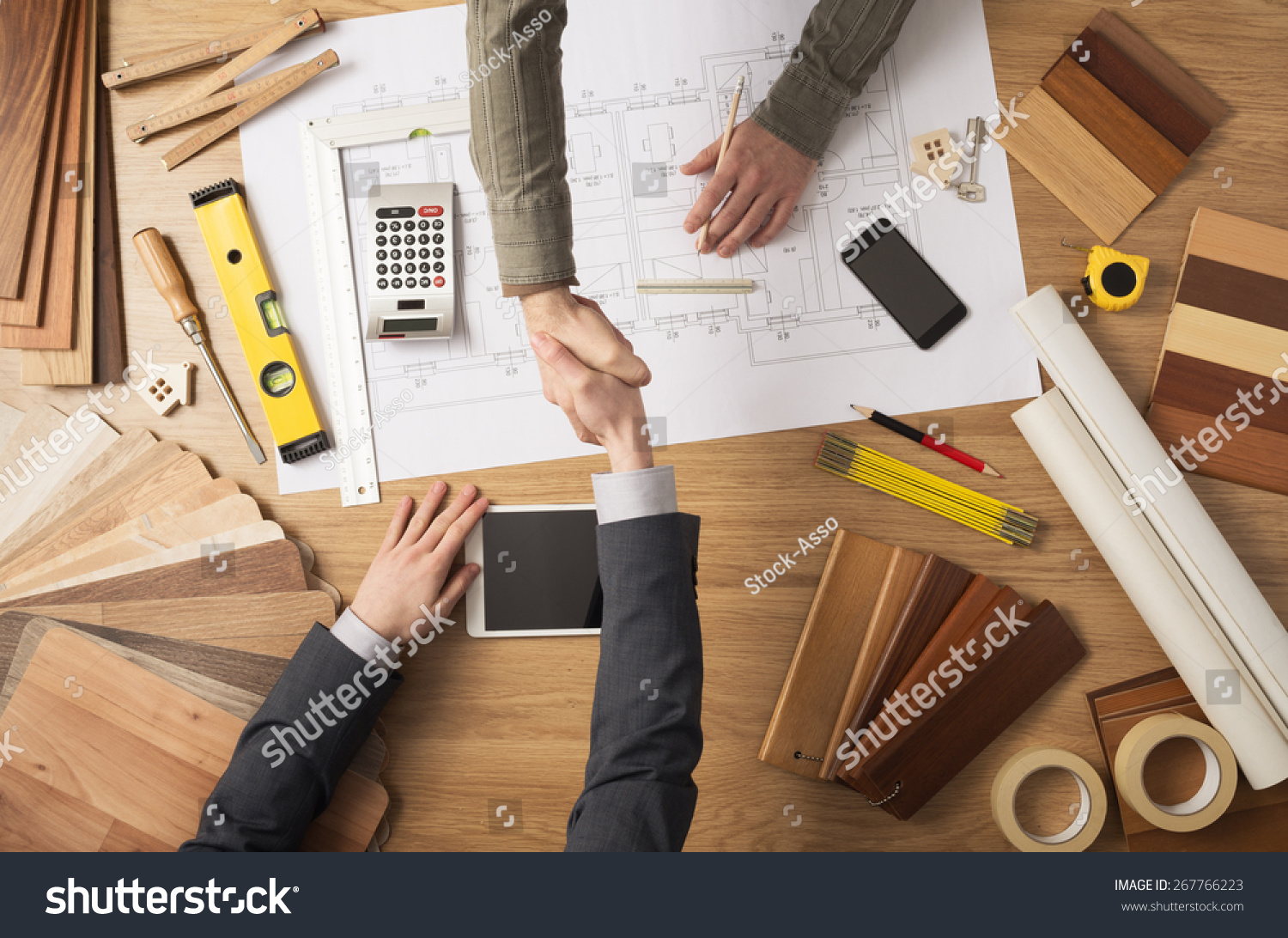 Architect and customer businessman shaking hands top view, desktop with building project, tools and wood swatches on background #267766223