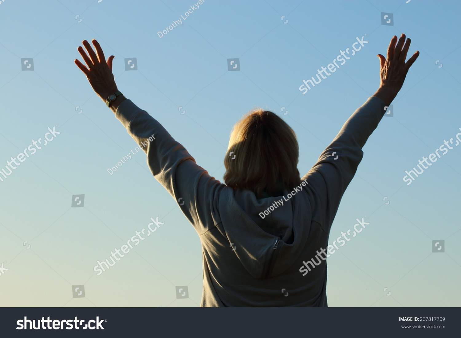Mature woman with her hands to the sky in worship and praise and/or feeling