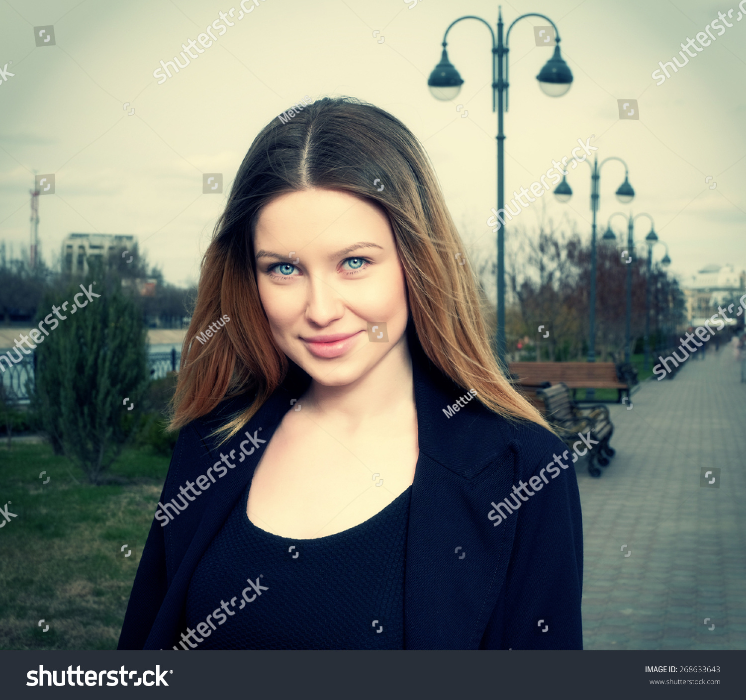 Smiling blond haired women toned instagram style image outdoors in the park front view head and shoulders shot