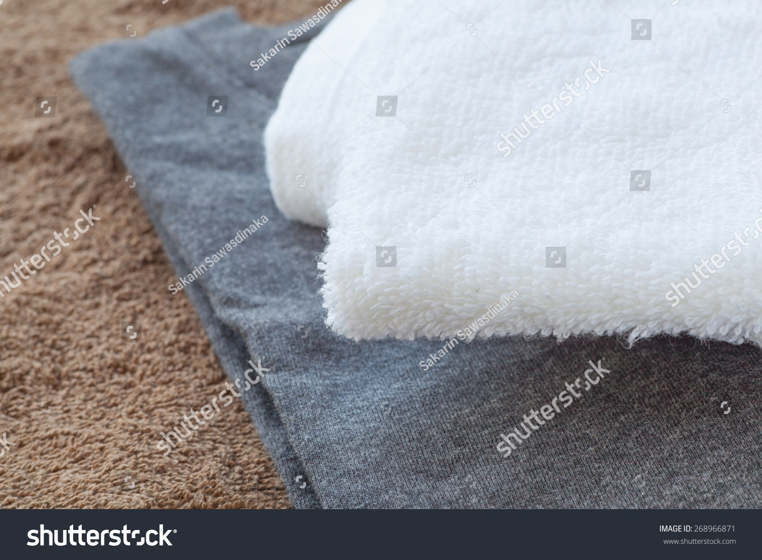 White towel and black t - shirt on brown towel background #268966871