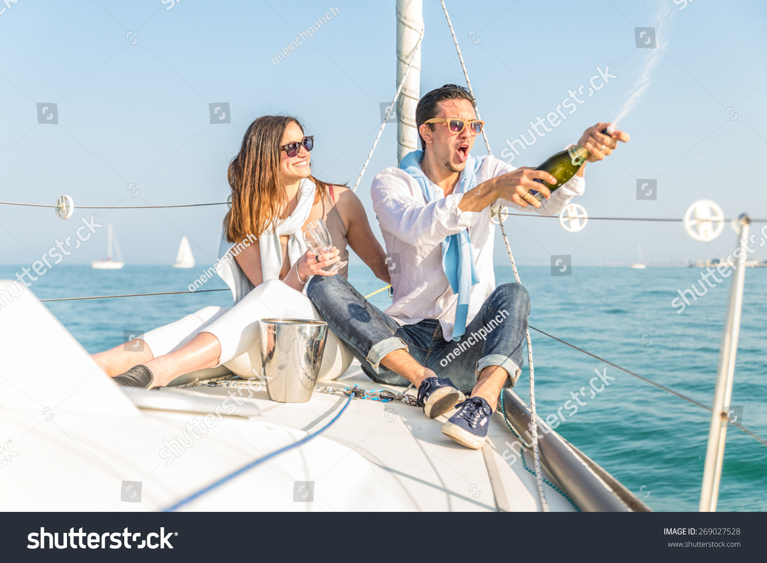 Couple celebrating with champagne on a boat Attractive man uncorking champagne and having party with girlfriend on vacation.Two young tourists having fun on boat tour in the summertime