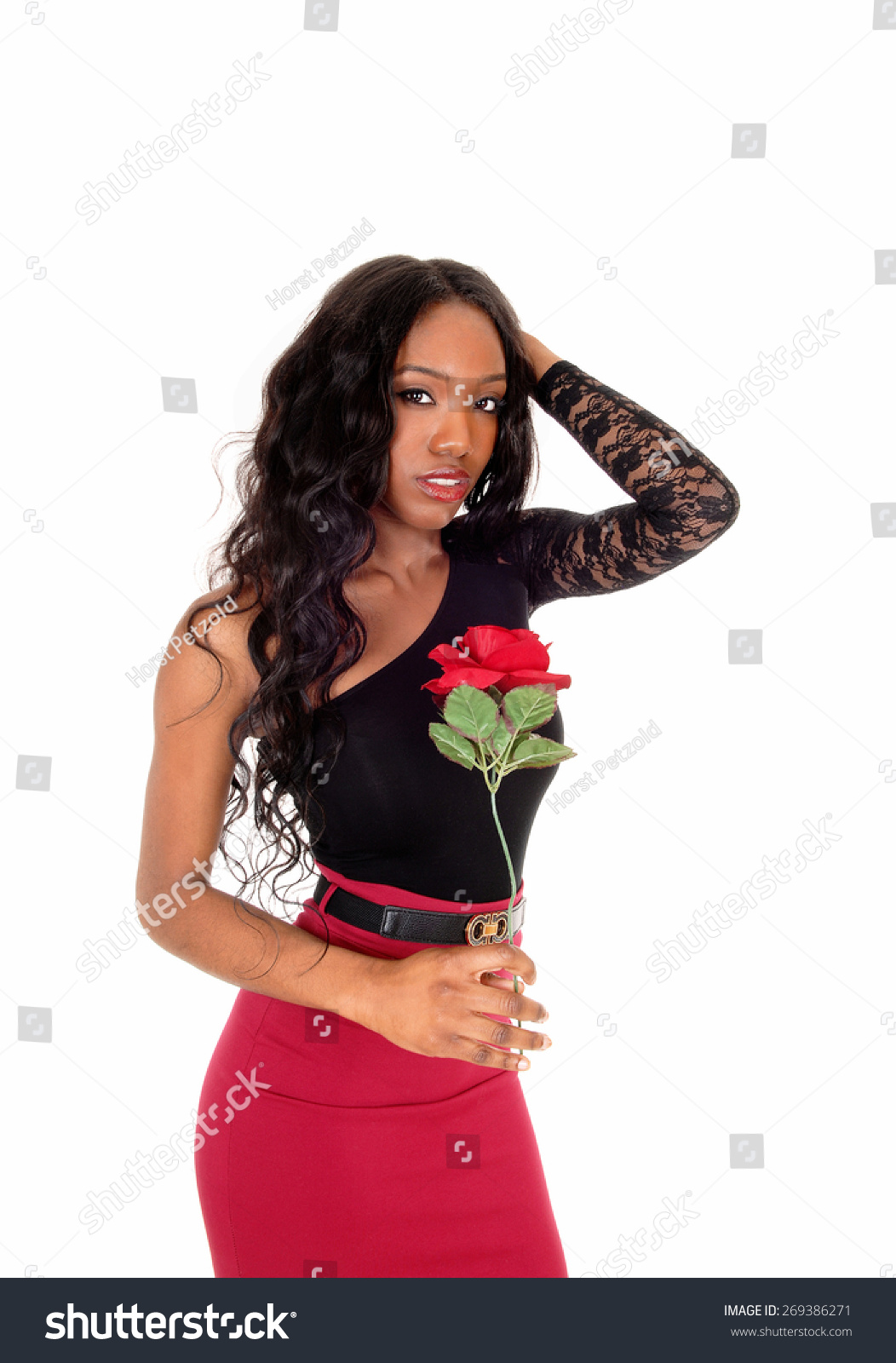 9ccadeb6a1 A lovely African American woman in a red skirt and black blouse standing in  the studio