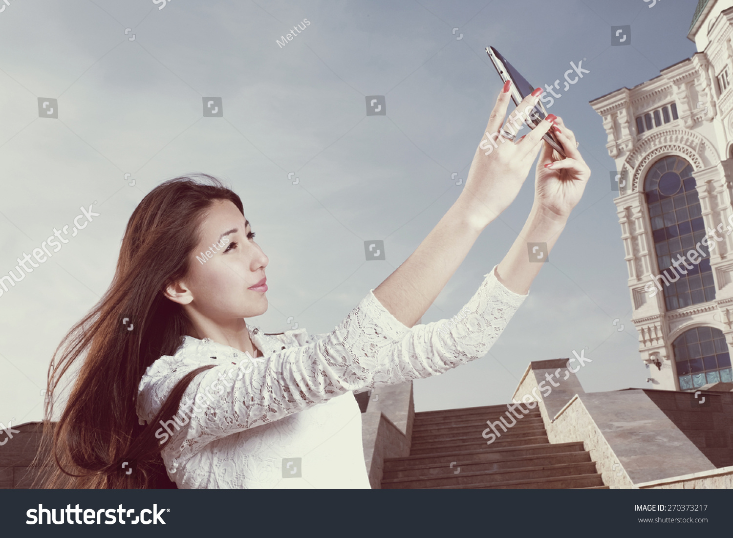 Instagram style vintage image iGen Girl Selfie. Young japanese women with long hair do selfie in city park afainst steps and clear blue sky with light haze, copyspace on the sky