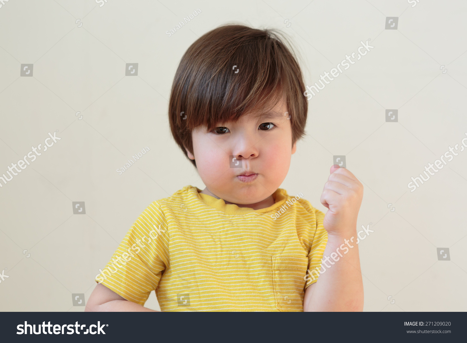 Tough toddler shaking fist. Terrible two year old. Small child punching,  hitting with pout on his face. Little boy with a big attitude. Moody kid.