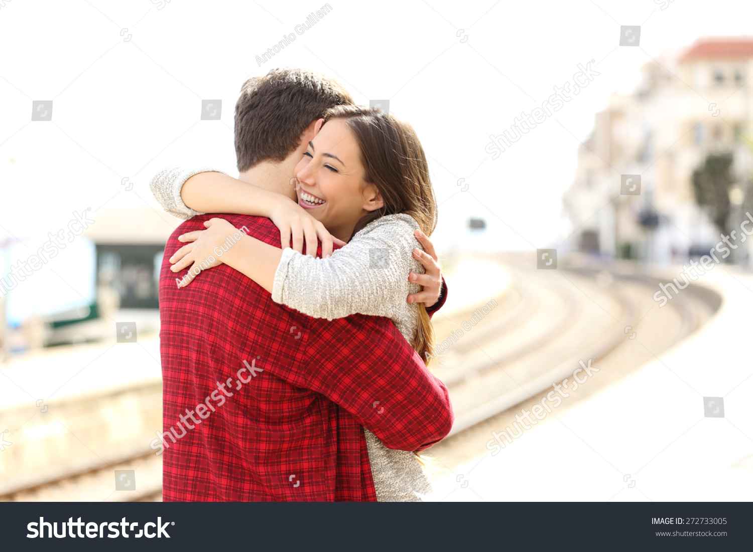 Happy couple hugging in a train station after arrival. Happy Couple Hugging Train Station After Stock Photo 272733005