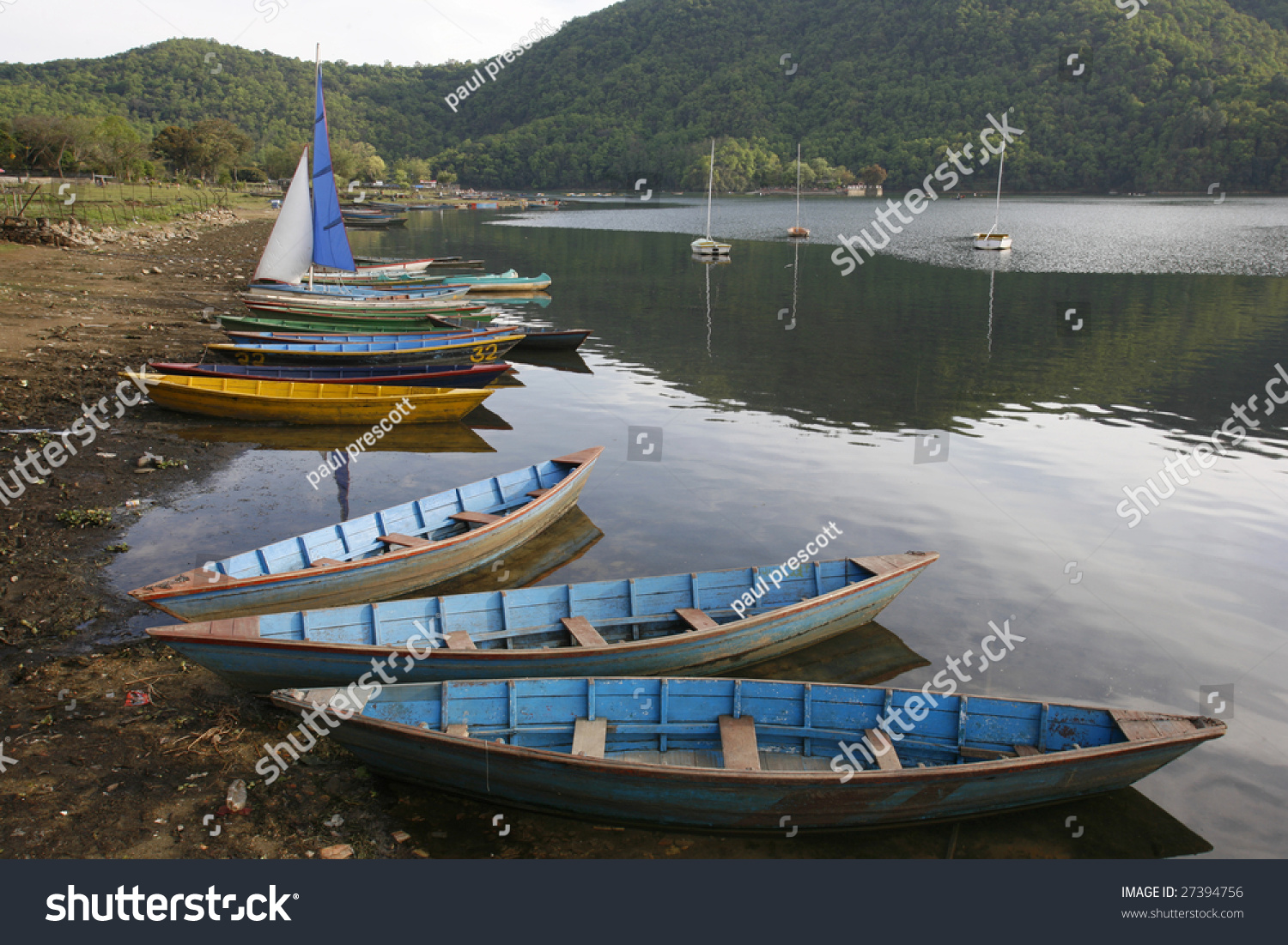 blue wooden boats floating on shore stock photo royalty free