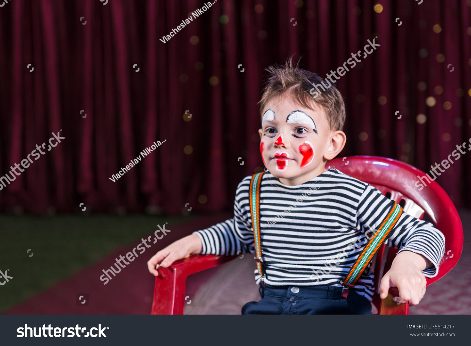 Cute kid with entertaining skills and clown make-up wearing striped long sleeve shirt and