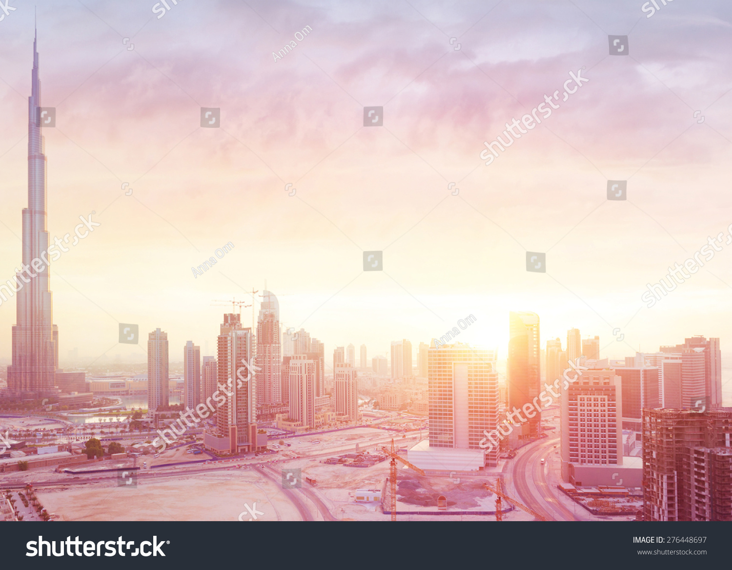 Beautiful sunset over Dubai city amazing cityscape lit with warm sun light contemporary new modern architecture view from above on a luxury property of United Arab Emirates