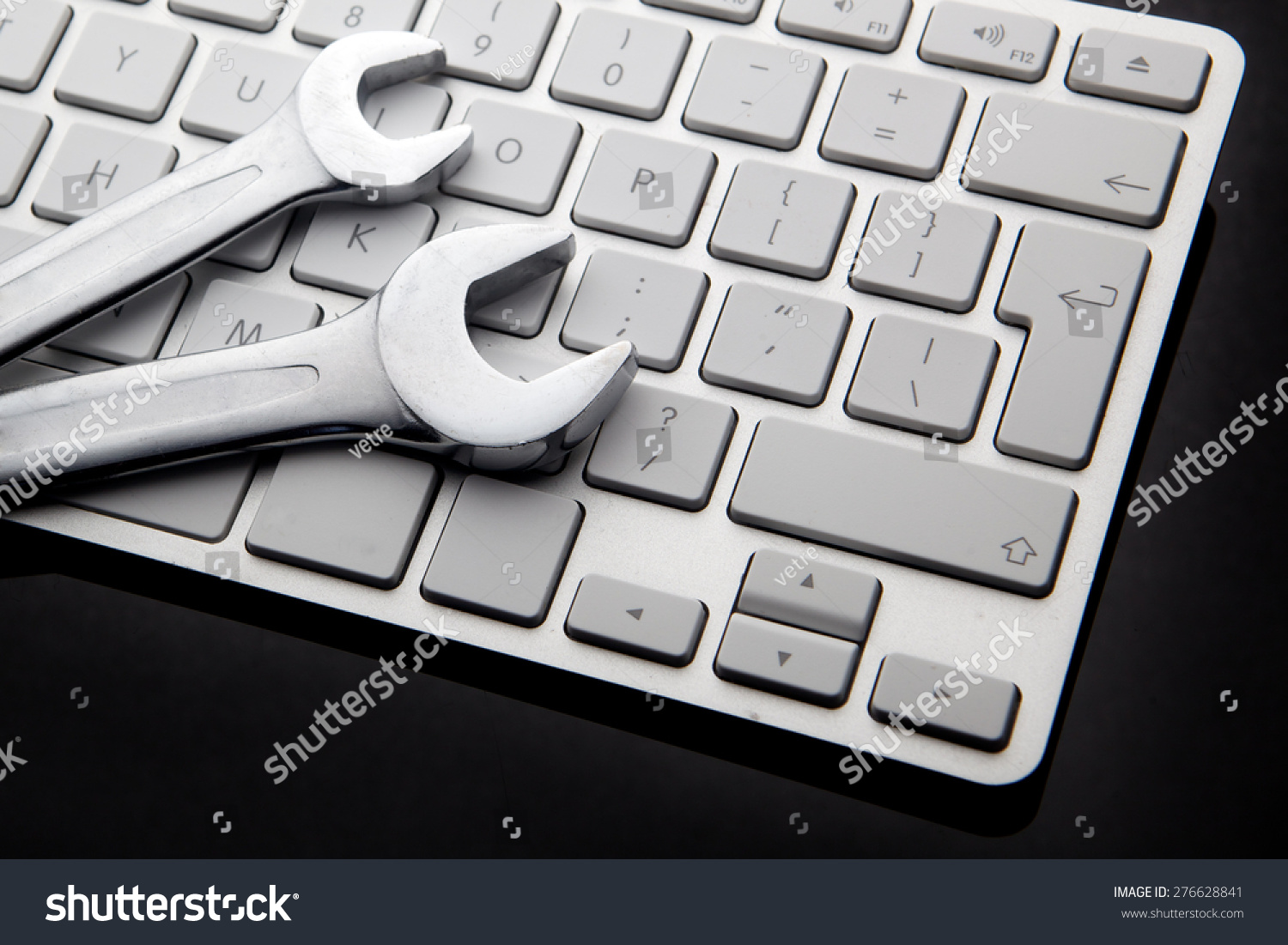 electronic technical support concept - spanners on computer keyboard #276628841
