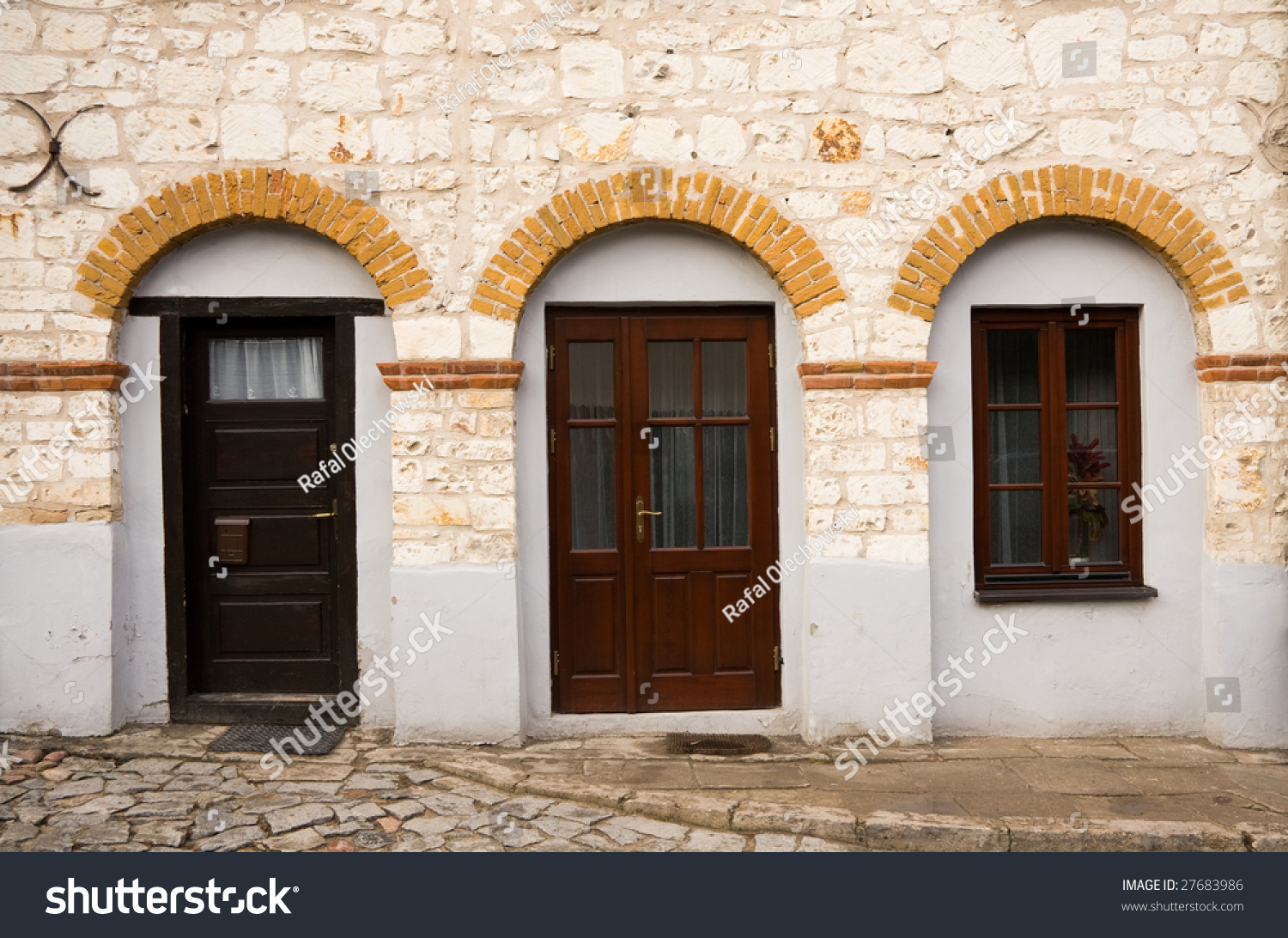 Vintage stone building facade with dark wood doors and for Stone building facade