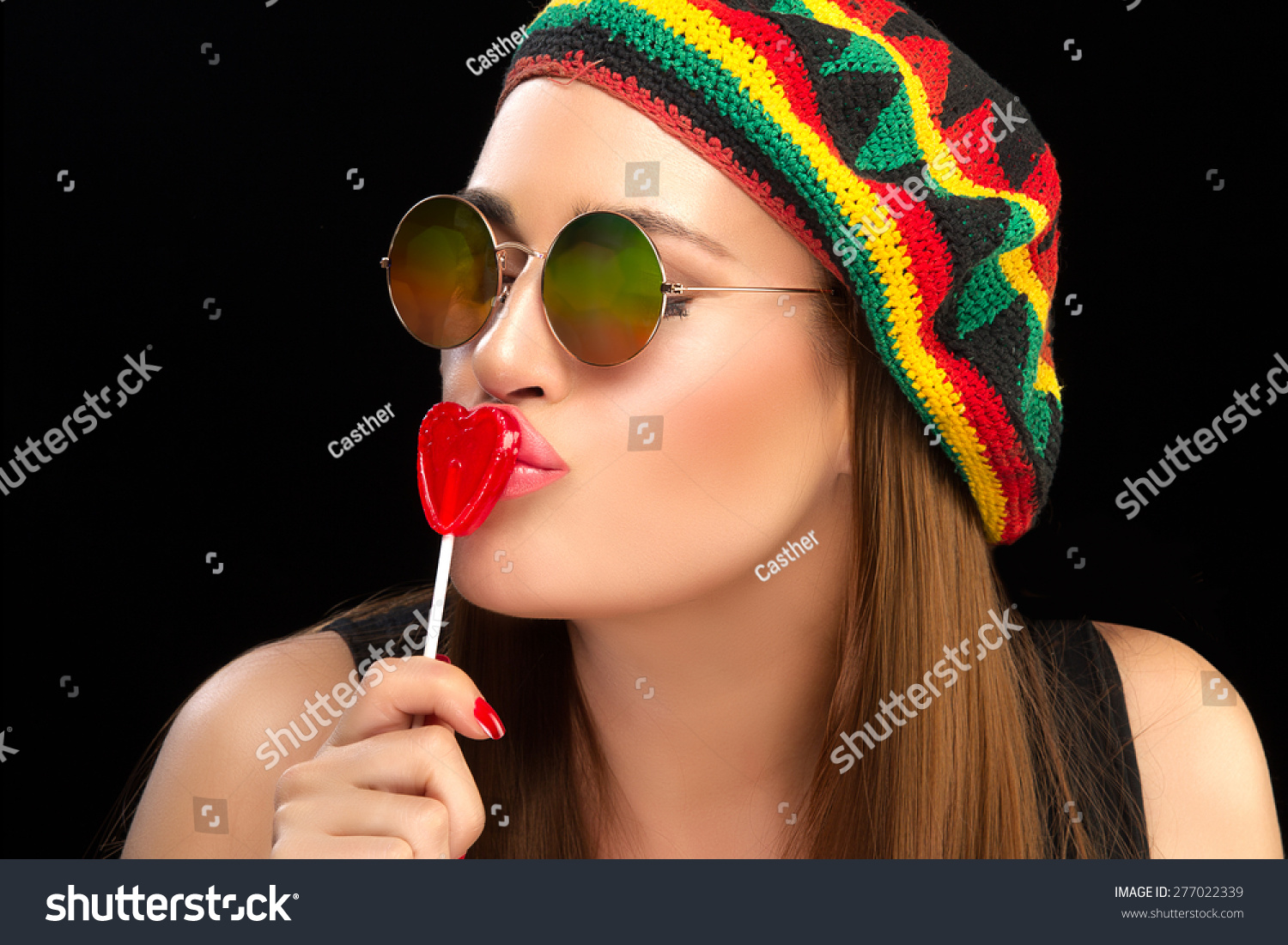 Stylish Young Pretty Woman in Rastafarian Hat and Trendy Sunglasses Kissing  a Heart Shaped Lollipop. 8a7c1d7d27e6