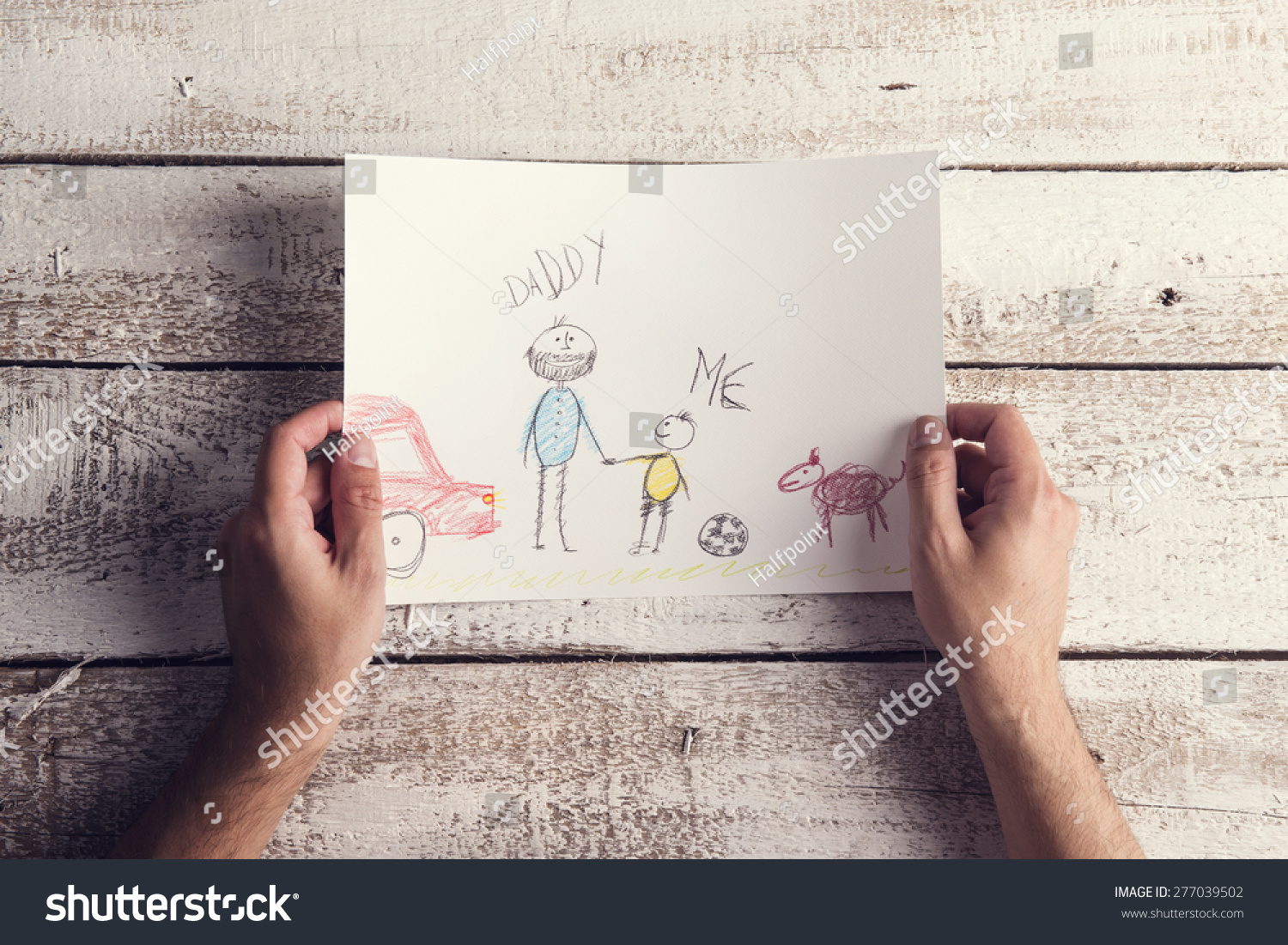 Day Composition With Childs Drawing Held By A Man Laid On Wooden Desk  1500 x 1101