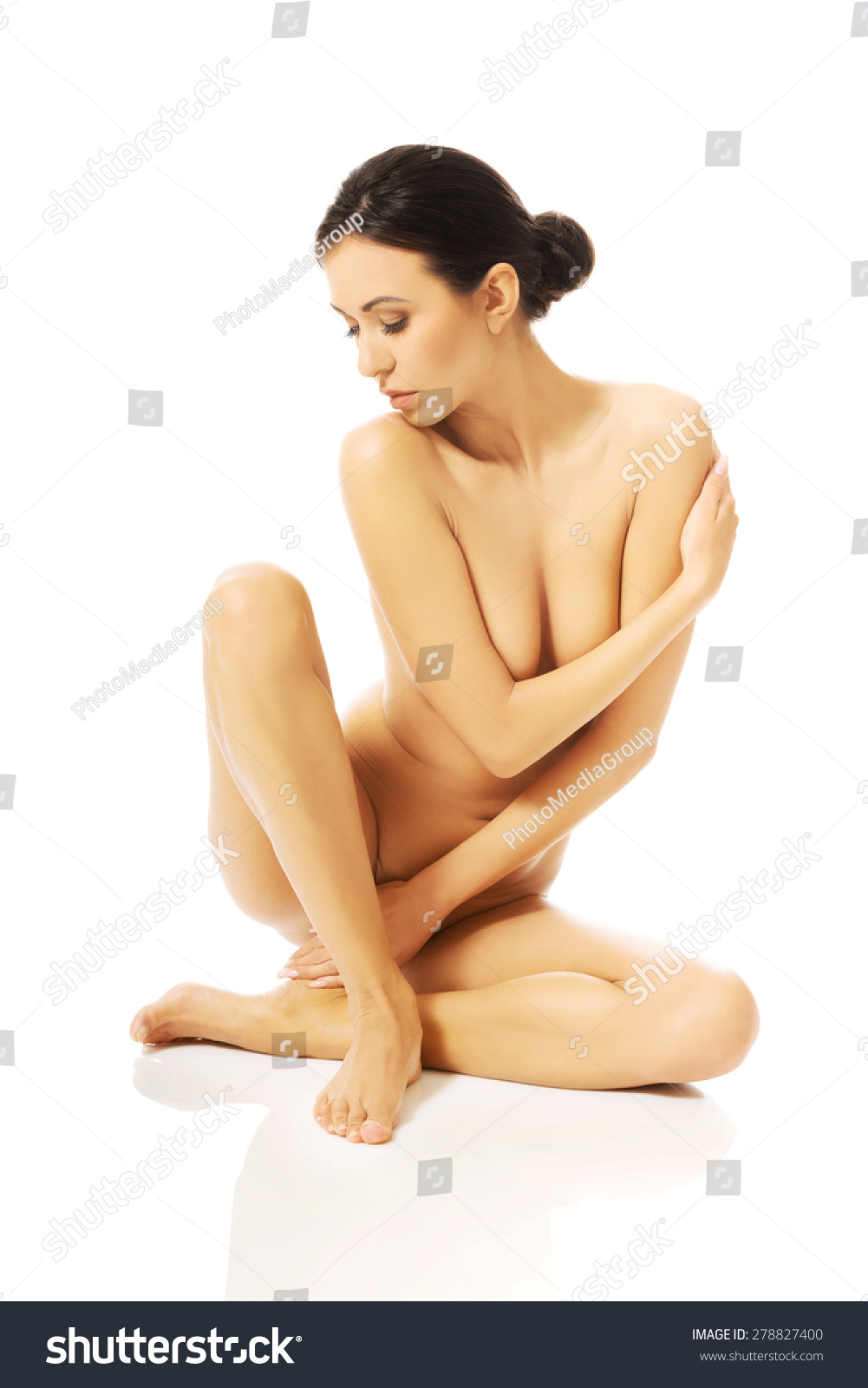 Full length photo of nude woman sitting cross legged and looking down.