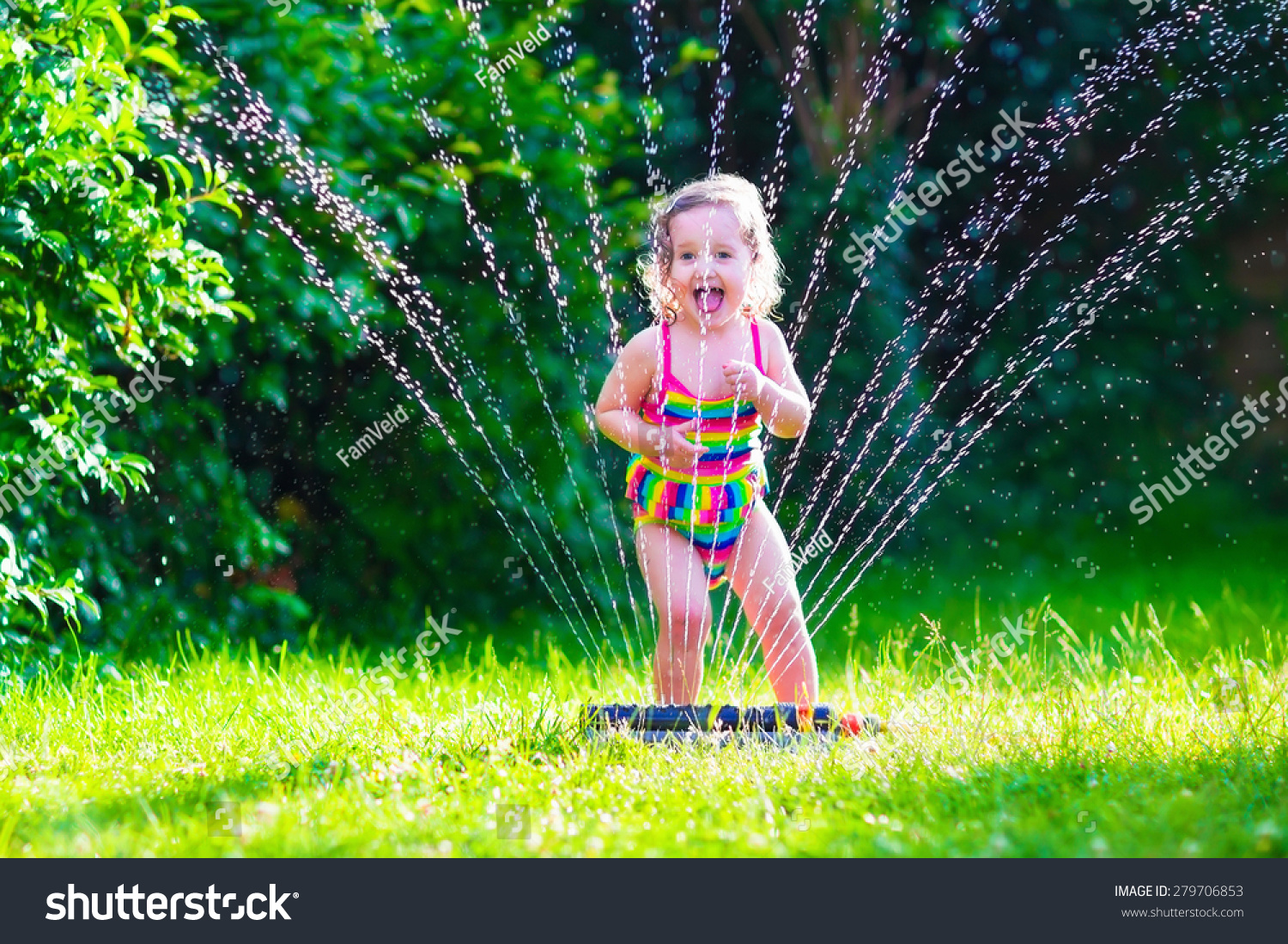 kids play water Child playing with garden sprinkler. Kid in bathing suit running and  jumping. Kids gardening