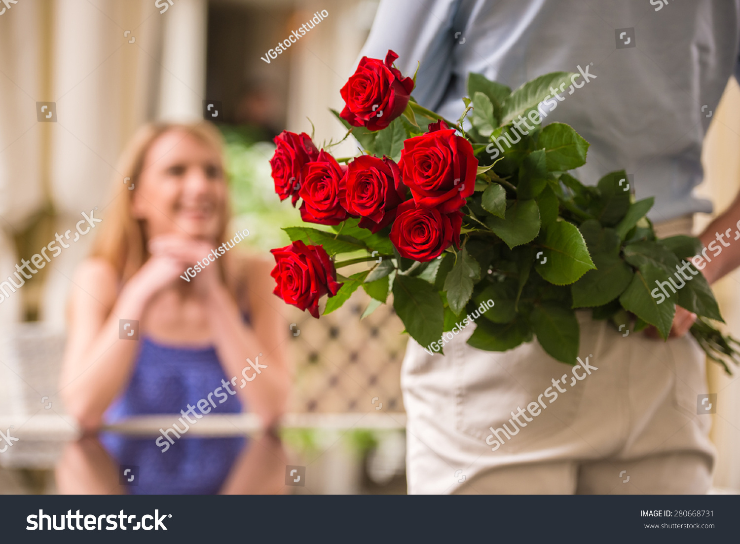 Young woman looking man flower bouquet stock photo royalty free young woman looking at man with flower bouquet behind the back izmirmasajfo Image collections
