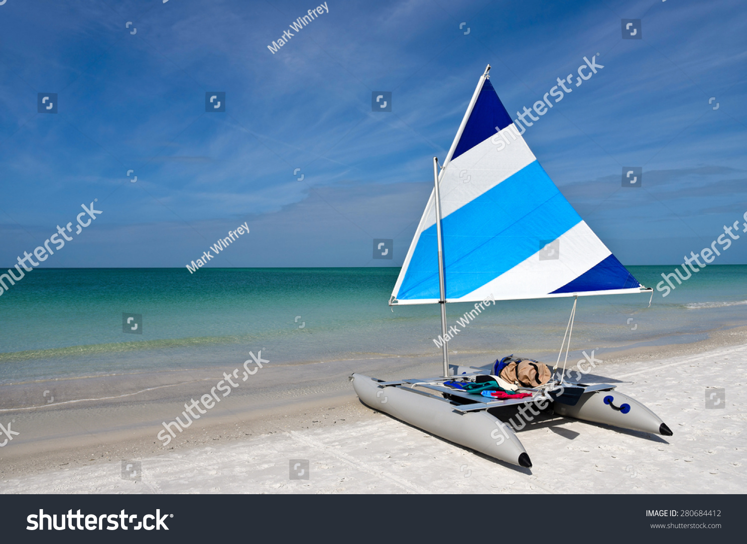 A Sailboat with a Blue and White Sail raised setting on the Beach
