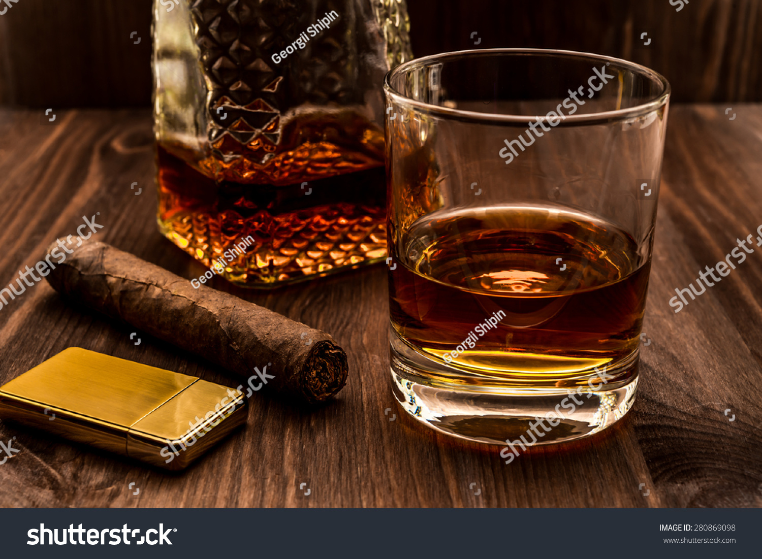 Decanter Of Whiskey And A Glass With Cuban Cigar And Golden Lighter On A  Wooden Table