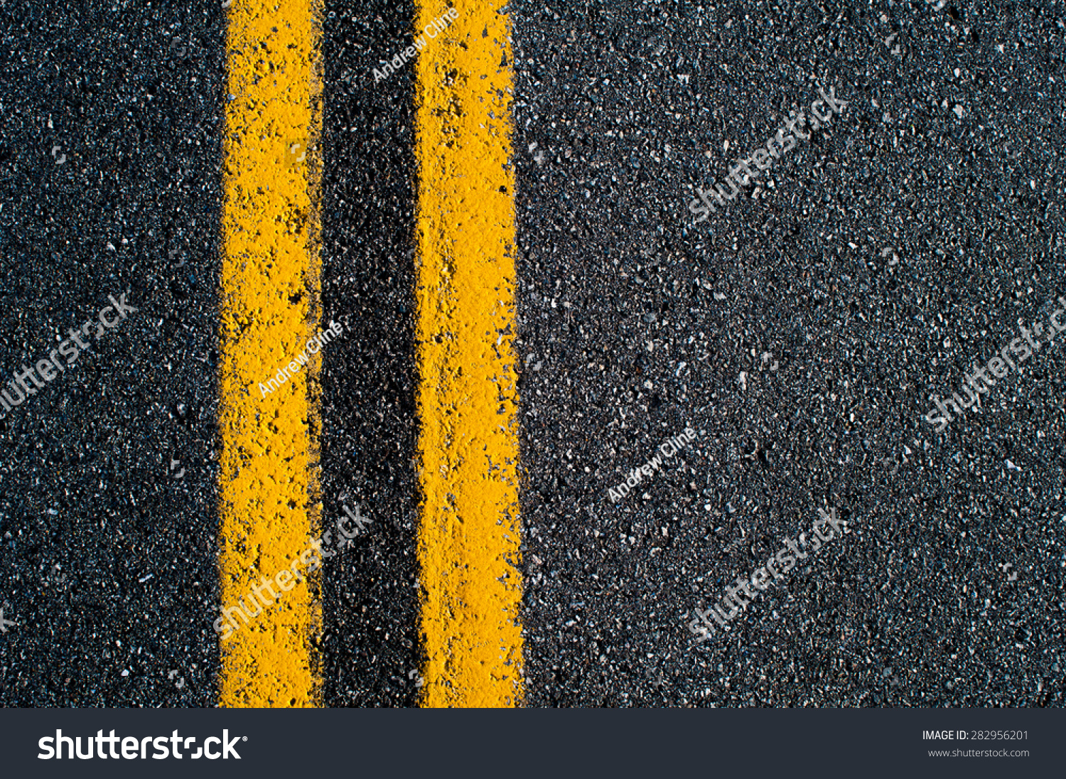 Double yellow line on black asphalt road.  #282956201