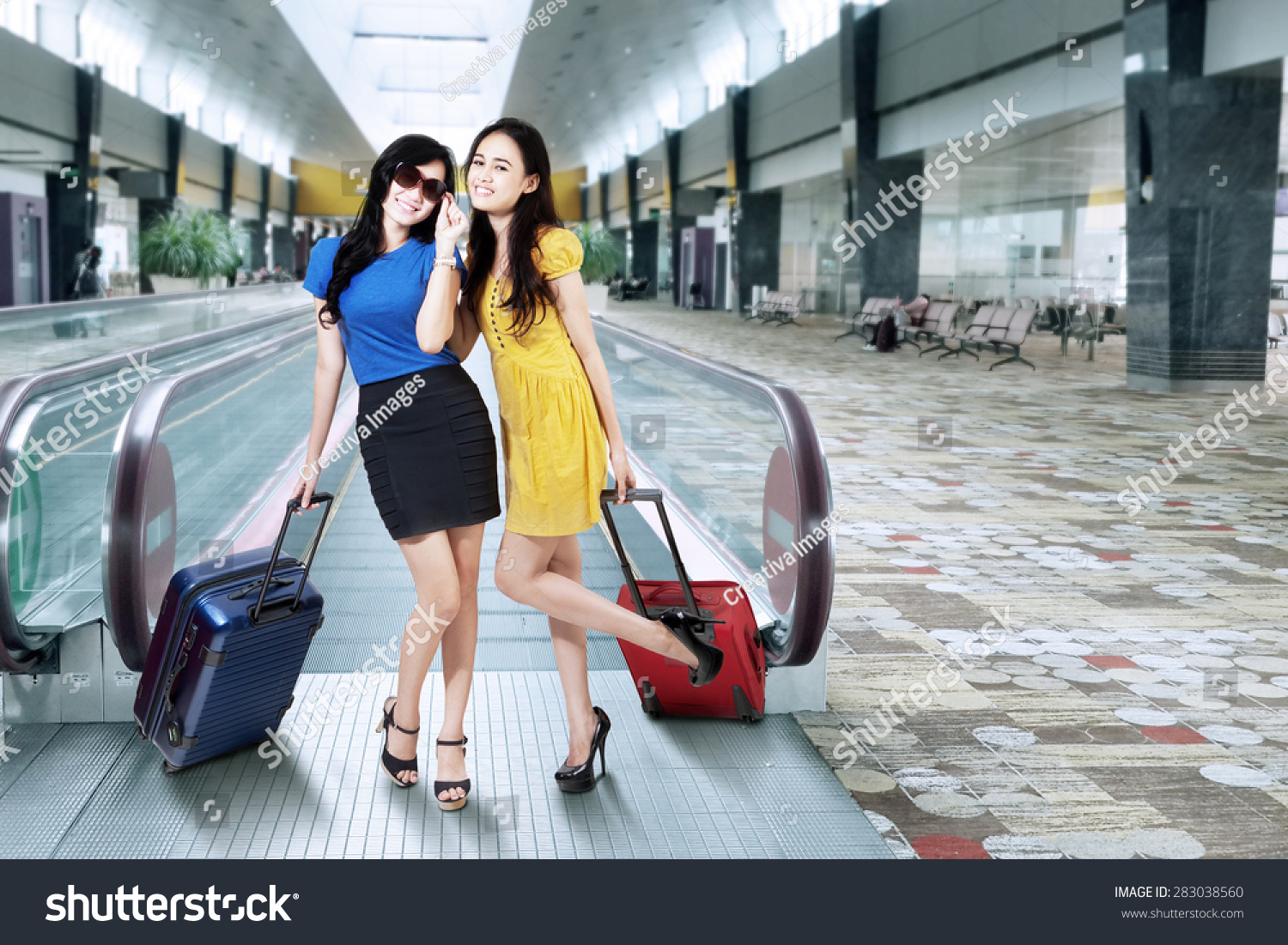 Portrait of two pretty girls traveling together and posing in the airport  hall 4da459eb7876d