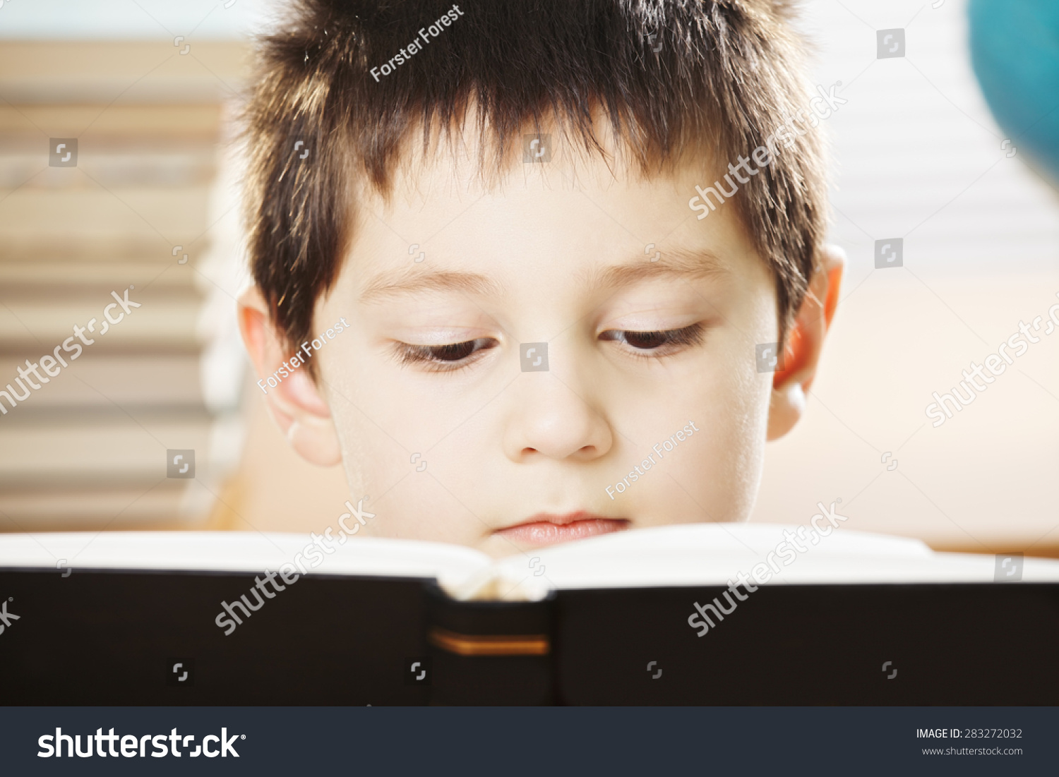 Black Boy Book Cover : Serious caucasian boy reading big book with black cover