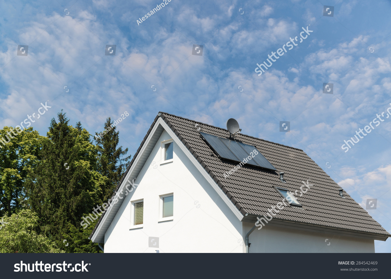 Modern House With Solar Panels And Trees Stock Photo