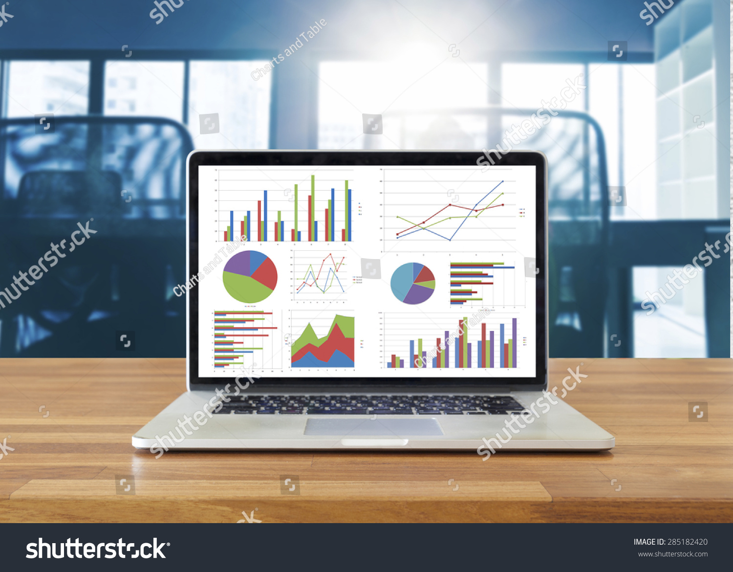 laptop on wooden table showing charts and graph against