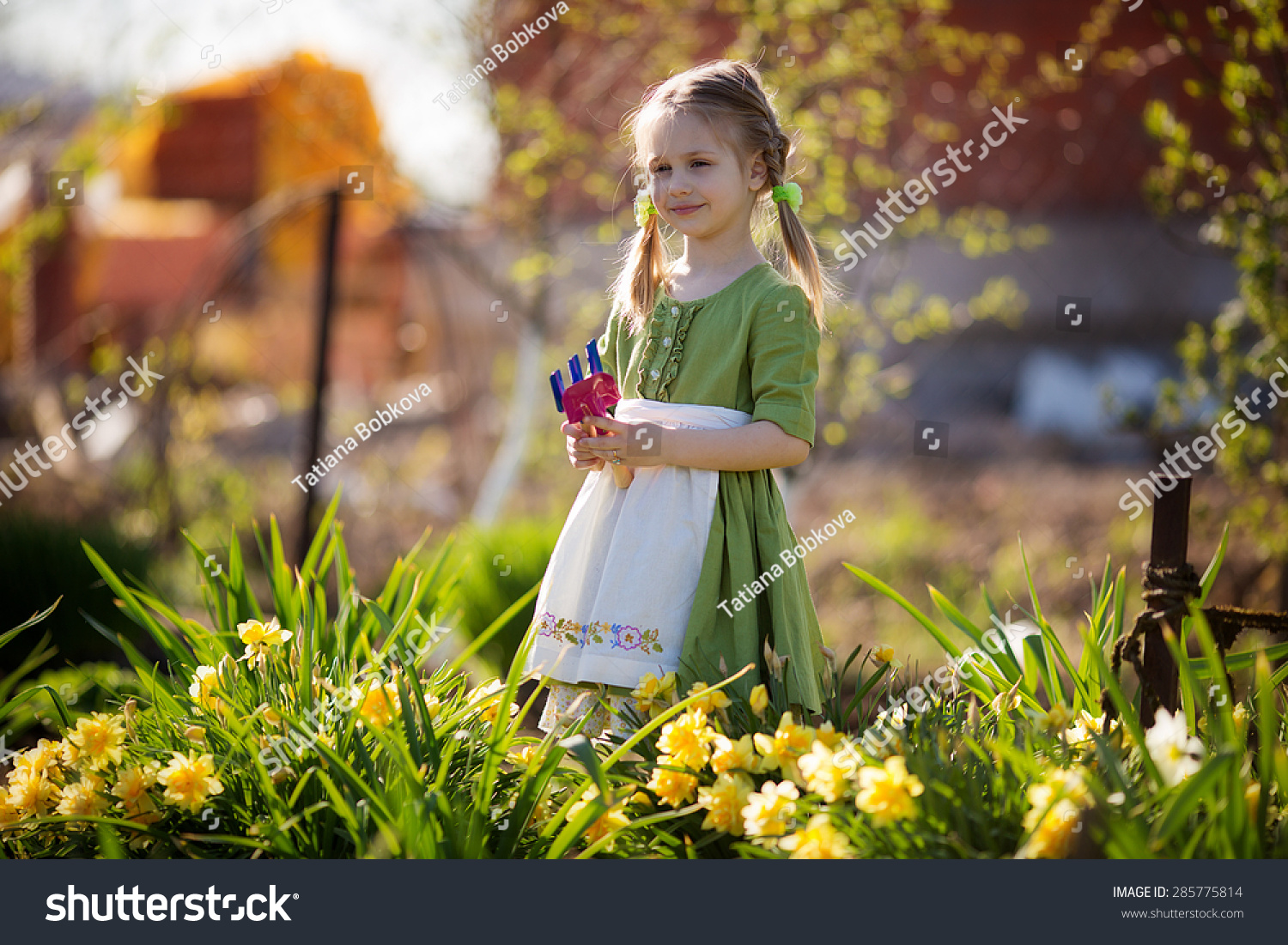 White apron girl - A Cute Little Girl In A Green Dress And White Apron Working In The Garden Among