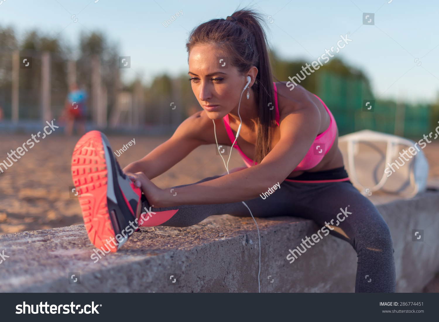 preteen stretch Fitness model athlete girl warm up stretching her hamstrings, leg and back. Young woman