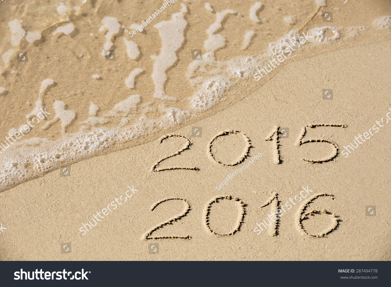 2015 2016 inscription written in the wet yellow beach sand being washed with sea water wave. Concept of celebrating the New Year at some exotic place #287494778