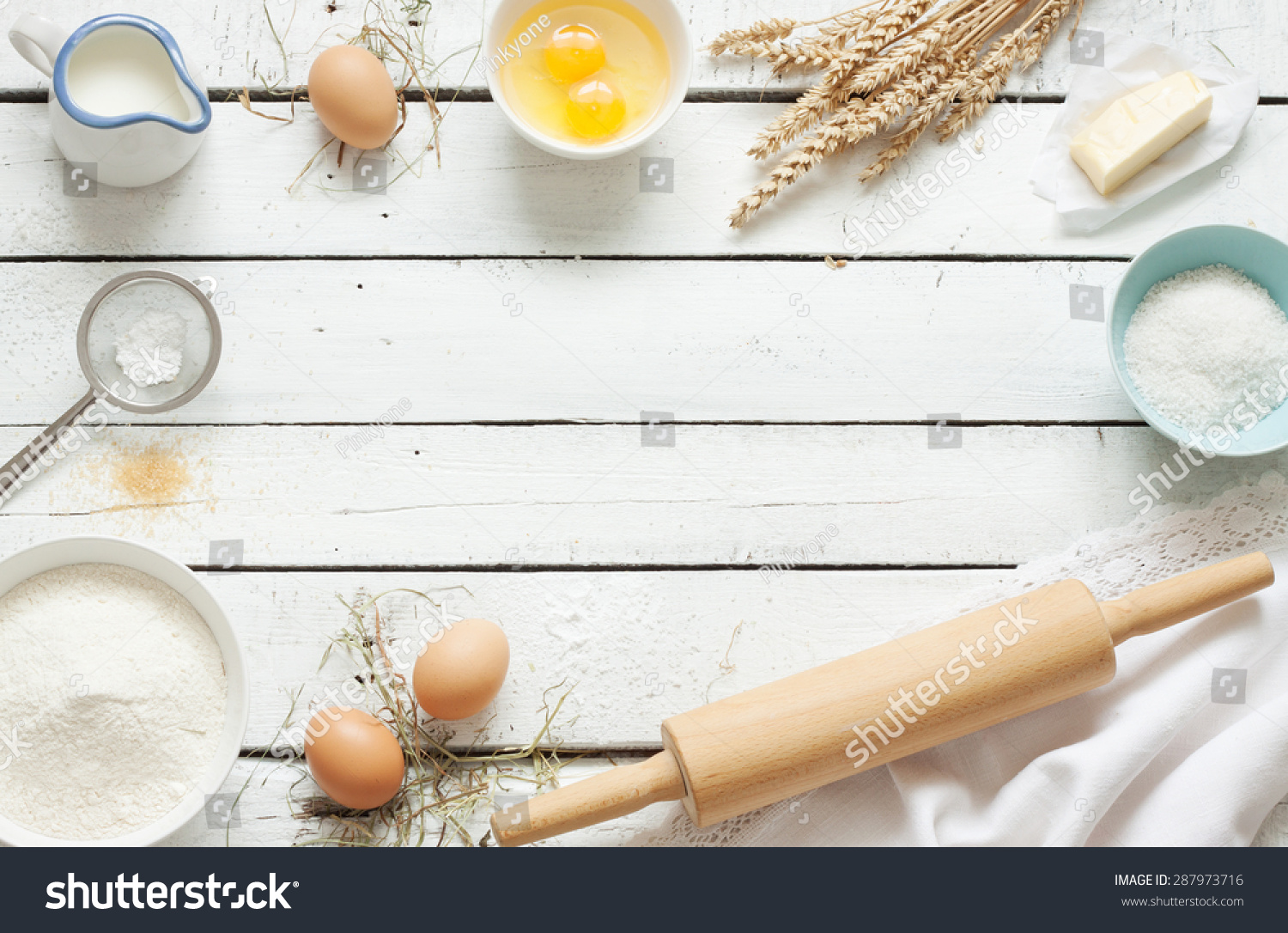 Baking cake in rustic kitchen - dough recipe ingredients (eggs, flour, milk, butter, sugar) on white planked wooden table from above. Background layout with free text space. #287973716