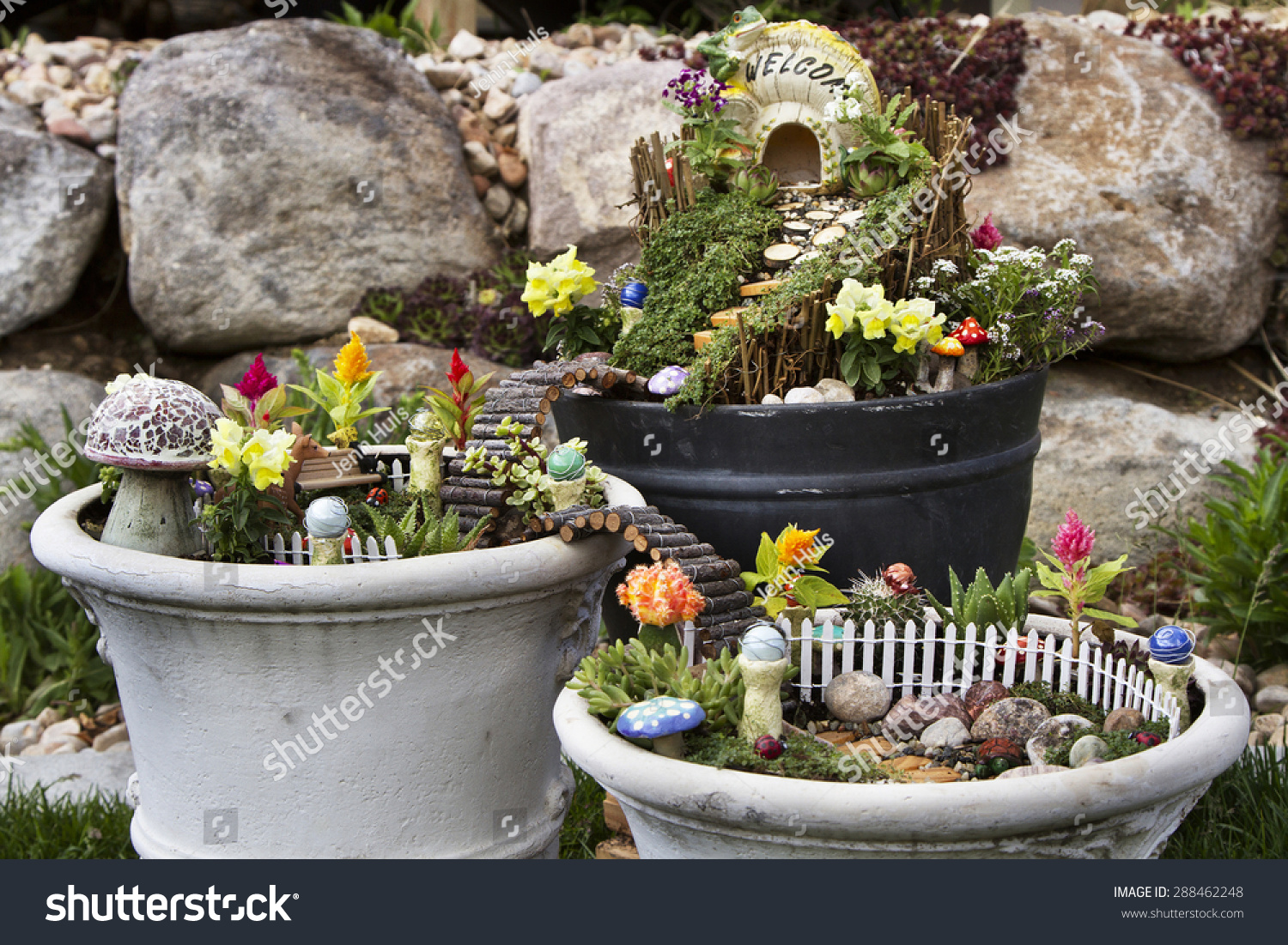 Fairy Garden In A Flower Pot With Walking Path, Wooden Bridges And A Fairy  House