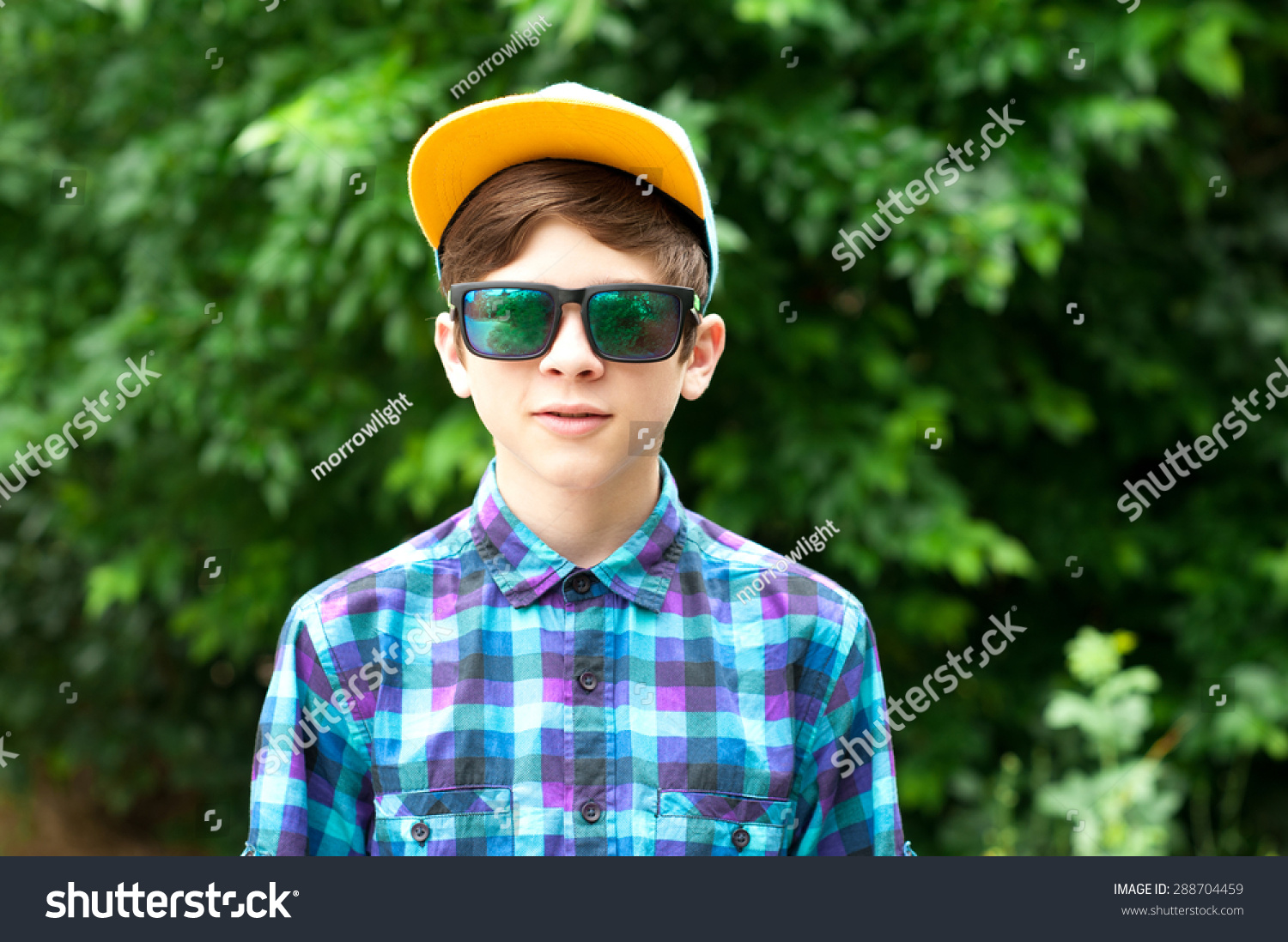 72be6f863674 Stylish teenage boy wearing sun glasses, cap and trendy shirt outdoors.  Looking at camera.