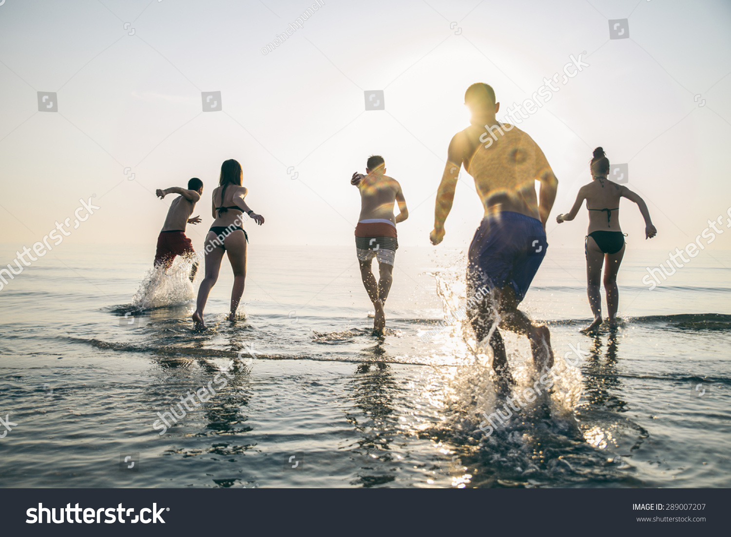 Group of happy friends running in to water at sunset - Silhouettes of active people having fun on the beach on vacation - Tourists going to swim on a tropical island #289007207