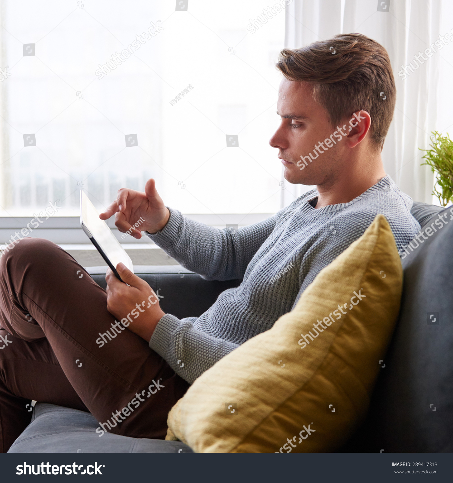 Profile Shot Of A Guy Using A Digital Tablet While Sitting ...